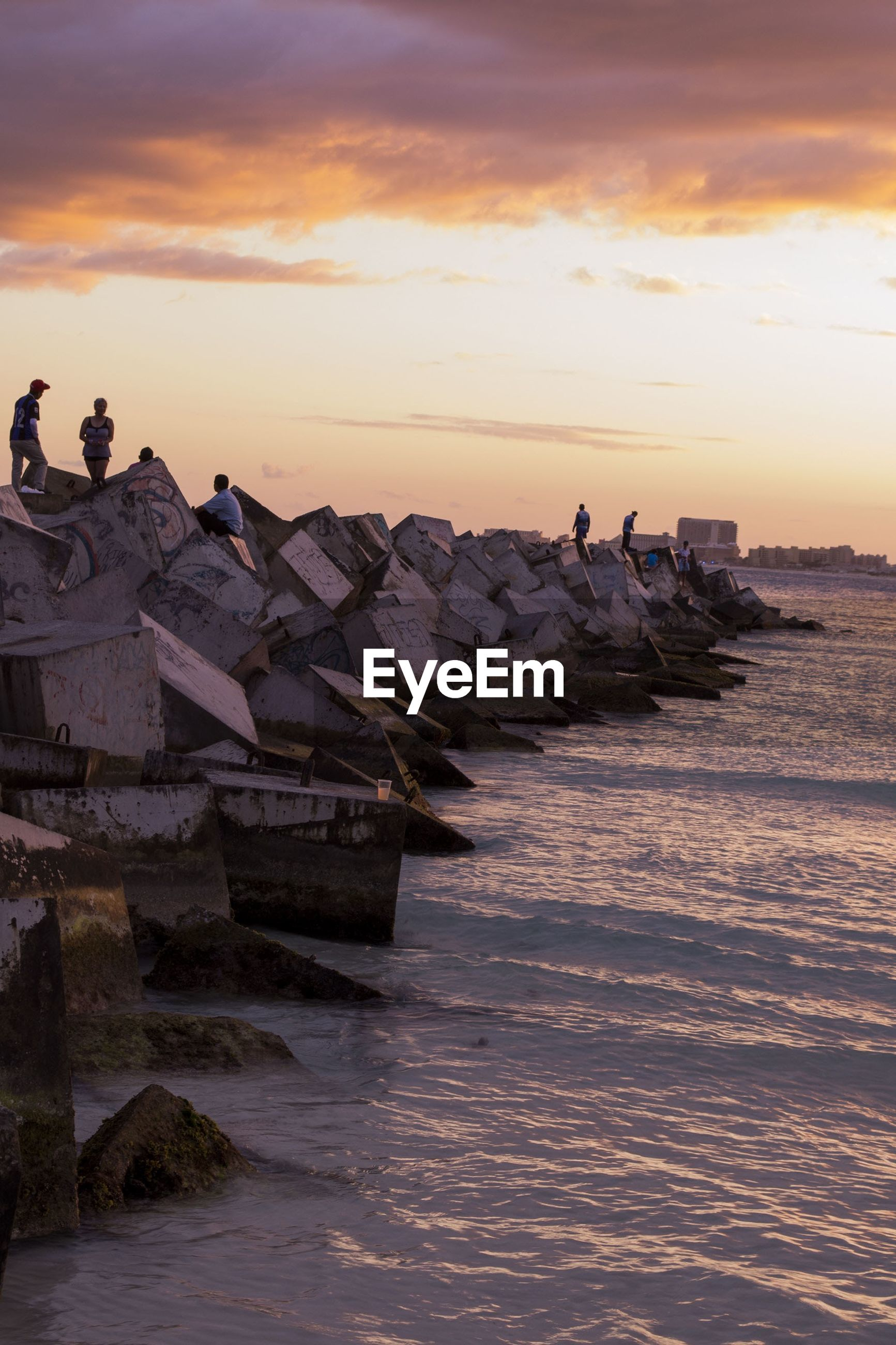 People on rocks by sea against sky during sunset
