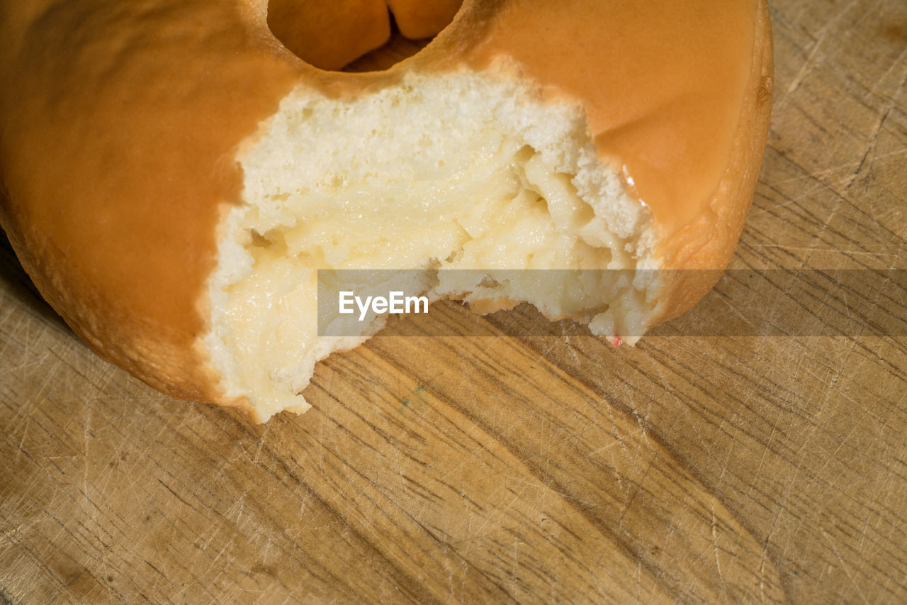 Close-Up Of Eaten Donut On Wooden Table