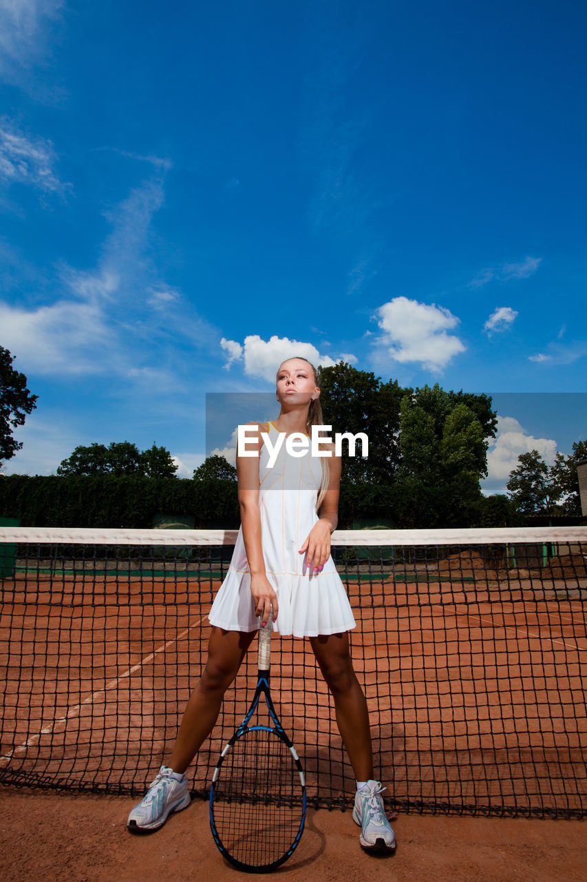 one person, sport, young adult, court, sky, full length, lifestyles, racket, tennis, tennis racket, real people, cloud - sky, women, leisure activity, young women, nature, standing, front view, clothing