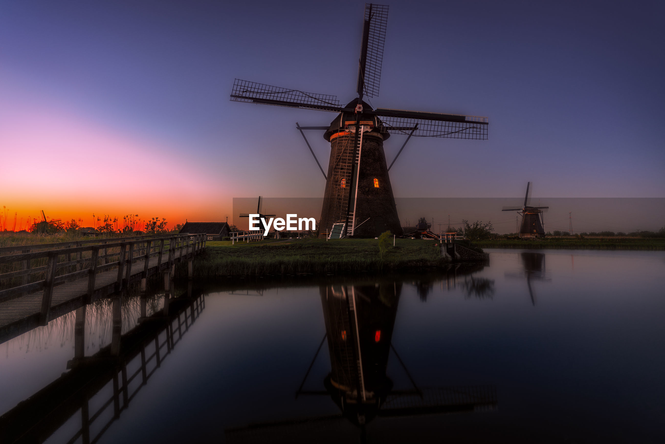 Traditional windmill by lake against dramatic sky during sunset