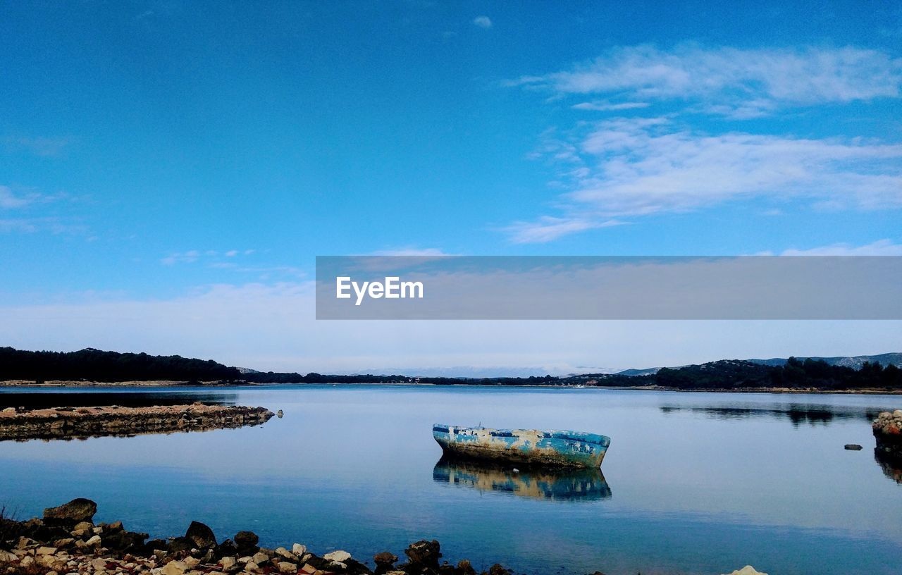 water, sky, nautical vessel, cloud - sky, tranquility, scenics - nature, transportation, beauty in nature, tranquil scene, nature, day, blue, no people, mode of transportation, reflection, lake, non-urban scene, idyllic, outdoors