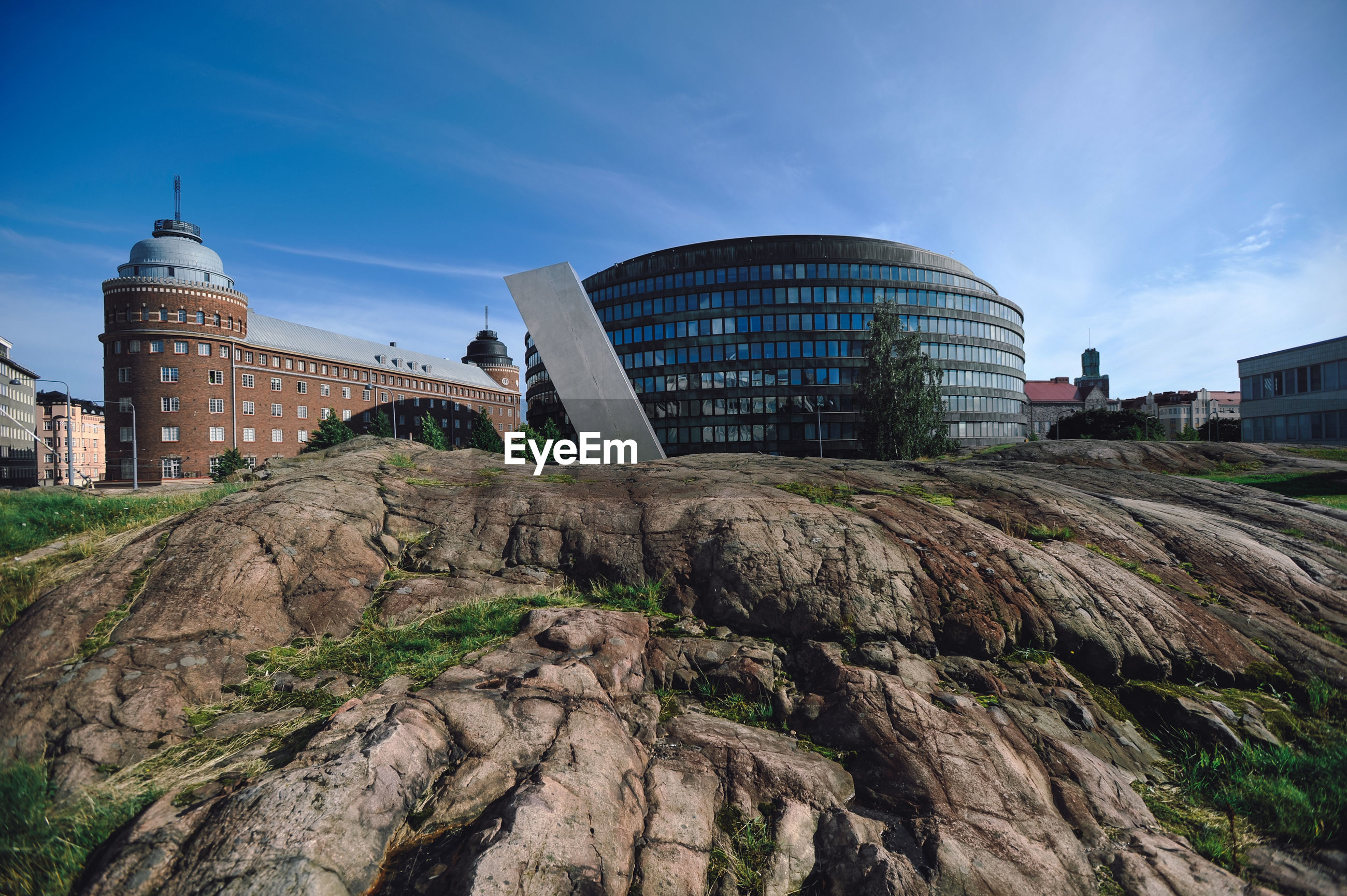 Modern building on rock in city against sky