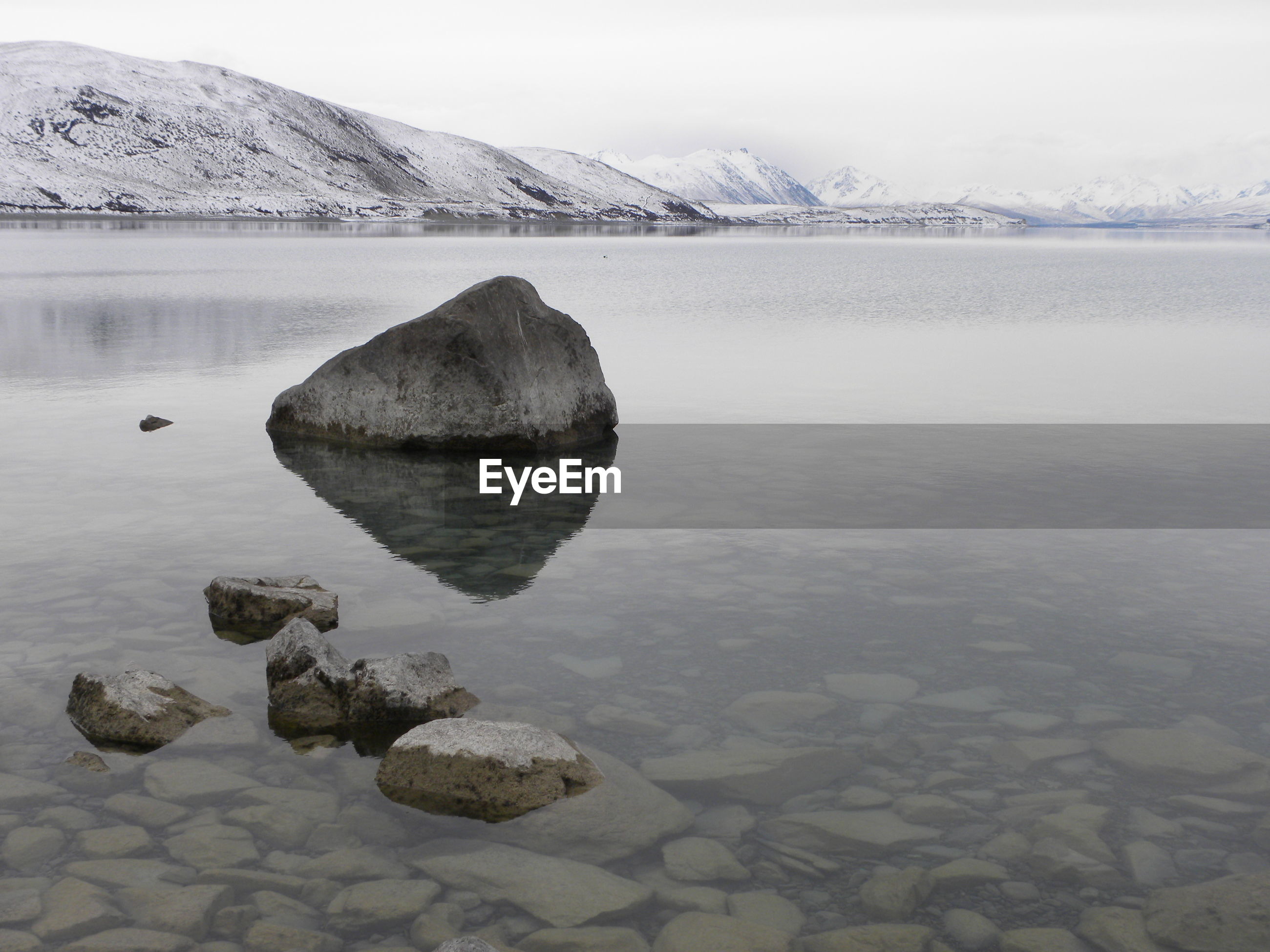 ROCKS BY LAKE AGAINST SNOWCAPPED MOUNTAINS