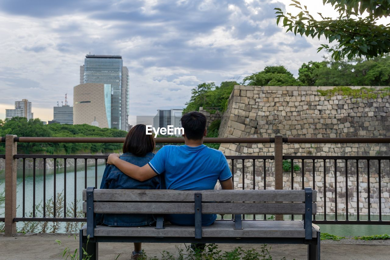 two people, rear view, architecture, bench, built structure, men, couple - relationship, togetherness, women, love, seat, leisure activity, real people, adult, bonding, building exterior, heterosexual couple, lifestyles, sitting, emotion, positive emotion, arm around, looking at view, park bench
