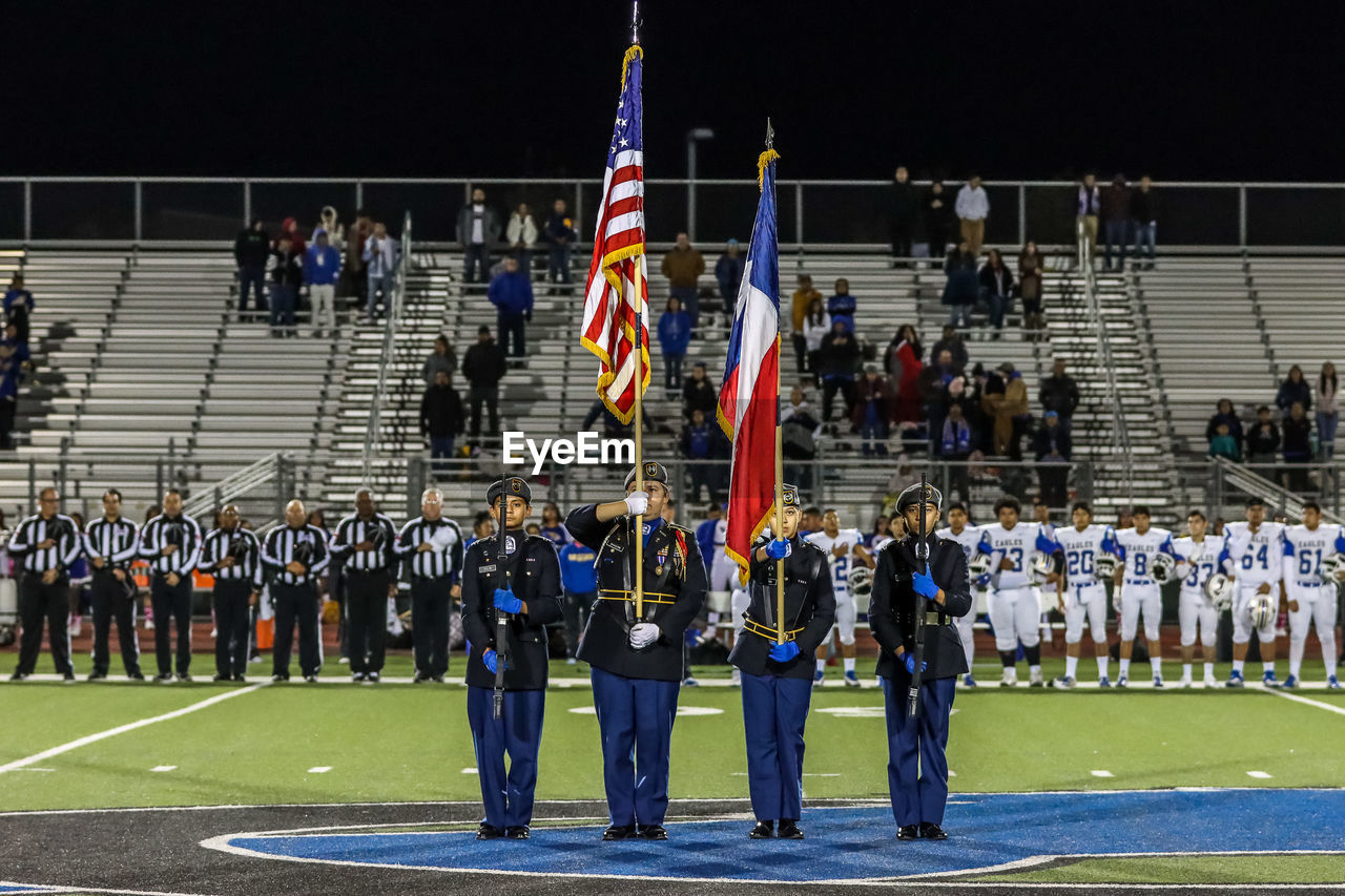 crowd, group of people, large group of people, real people, flag, men, patriotism, women, night, sport, lifestyles, clothing, city, architecture, outdoors, uniform, celebration, event, spectator, government