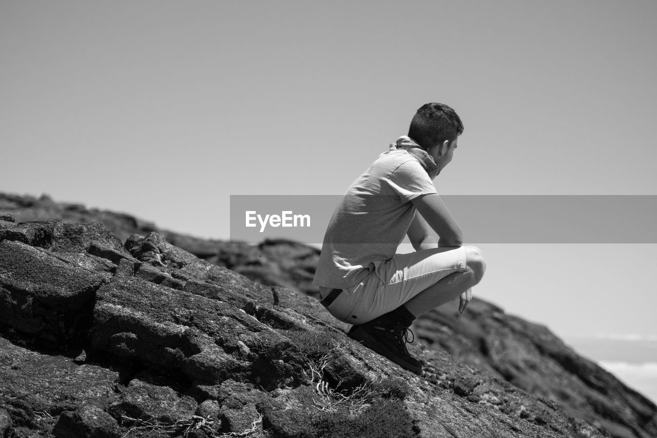 Man Crouching On Mountain Against Sky