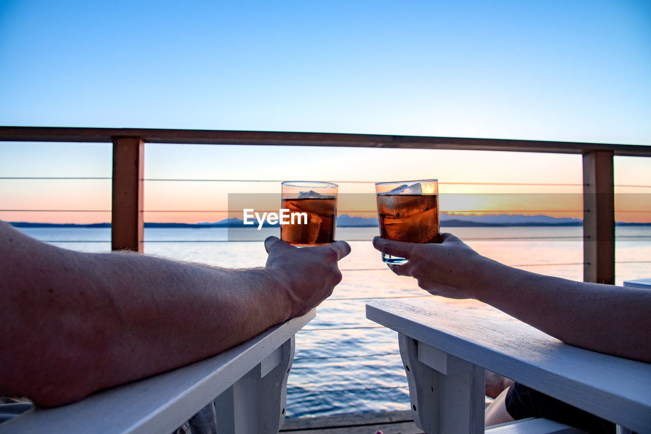 Cropped image of couple drinking whiskey on pier against sky