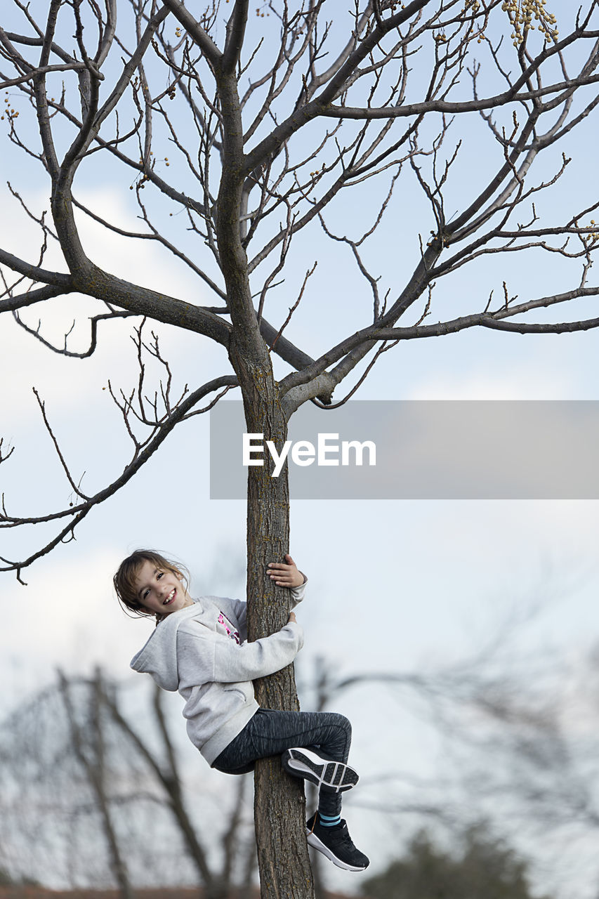 Side View Portrait Of Smiling Girl Climbing Tree Against Sky