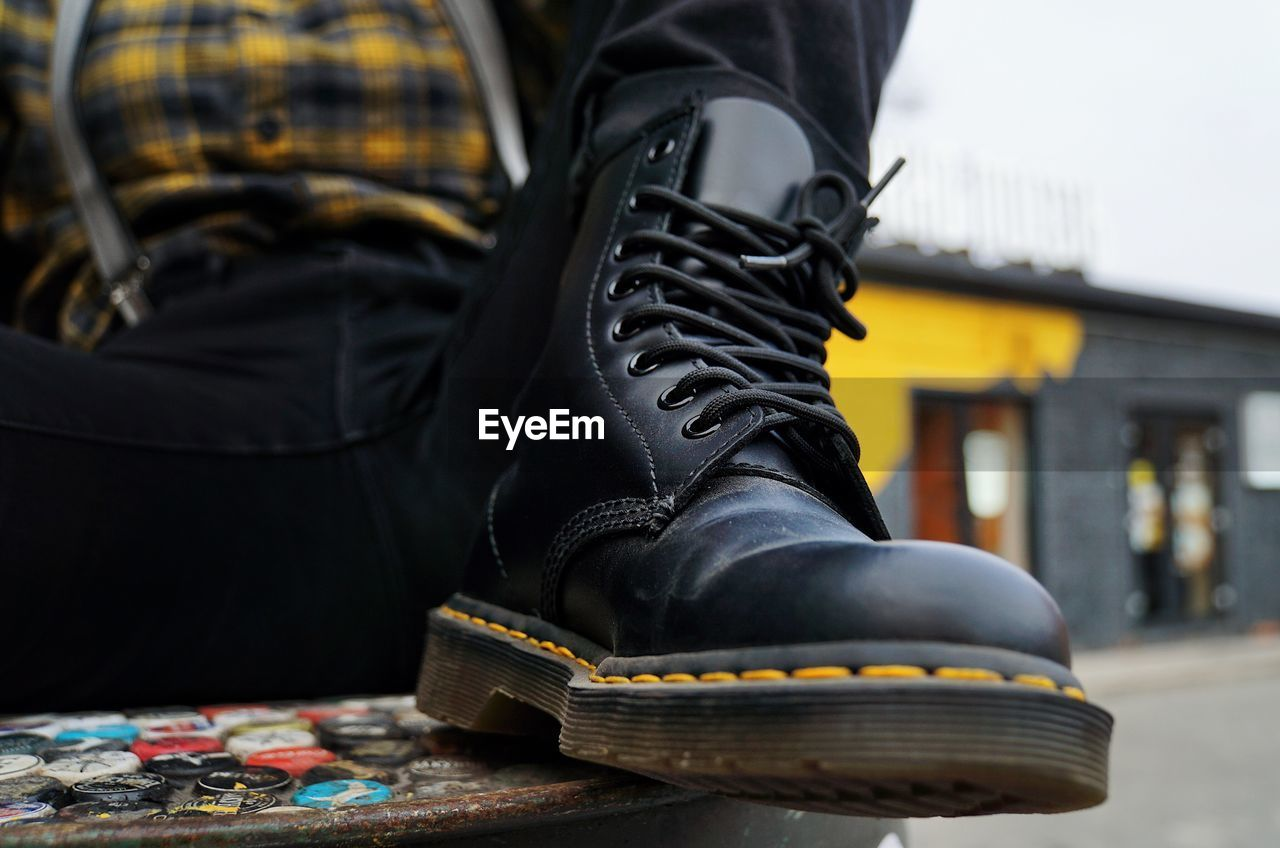 one person, shoe, low section, focus on foreground, human body part, human leg, body part, black color, real people, leisure activity, close-up, day, lifestyles, boot, standing, outdoors, architecture, casual clothing, yellow, leather, human foot, jeans