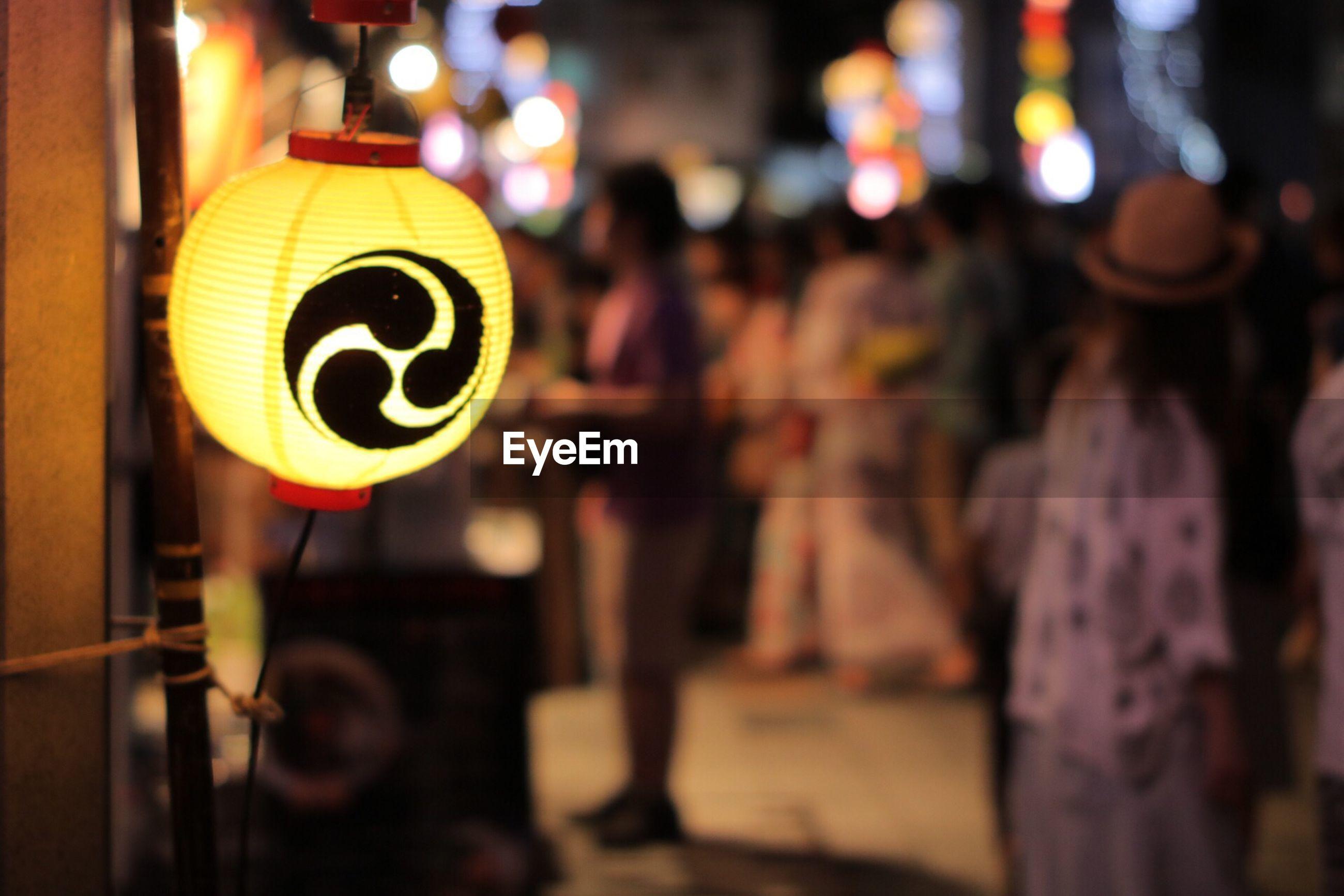 Close-up of illuminated yellow lantern on street at night