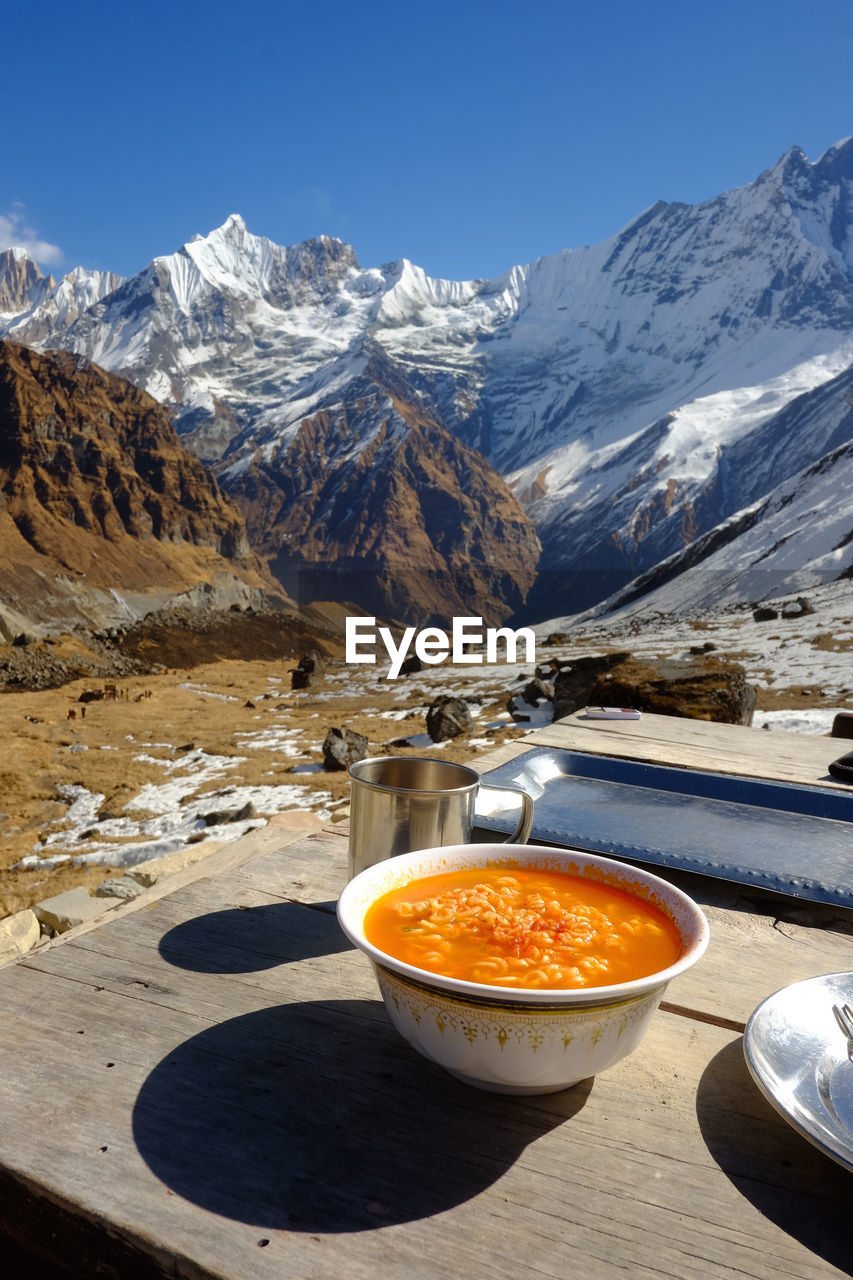 Food in bowl on table at mountain during winter