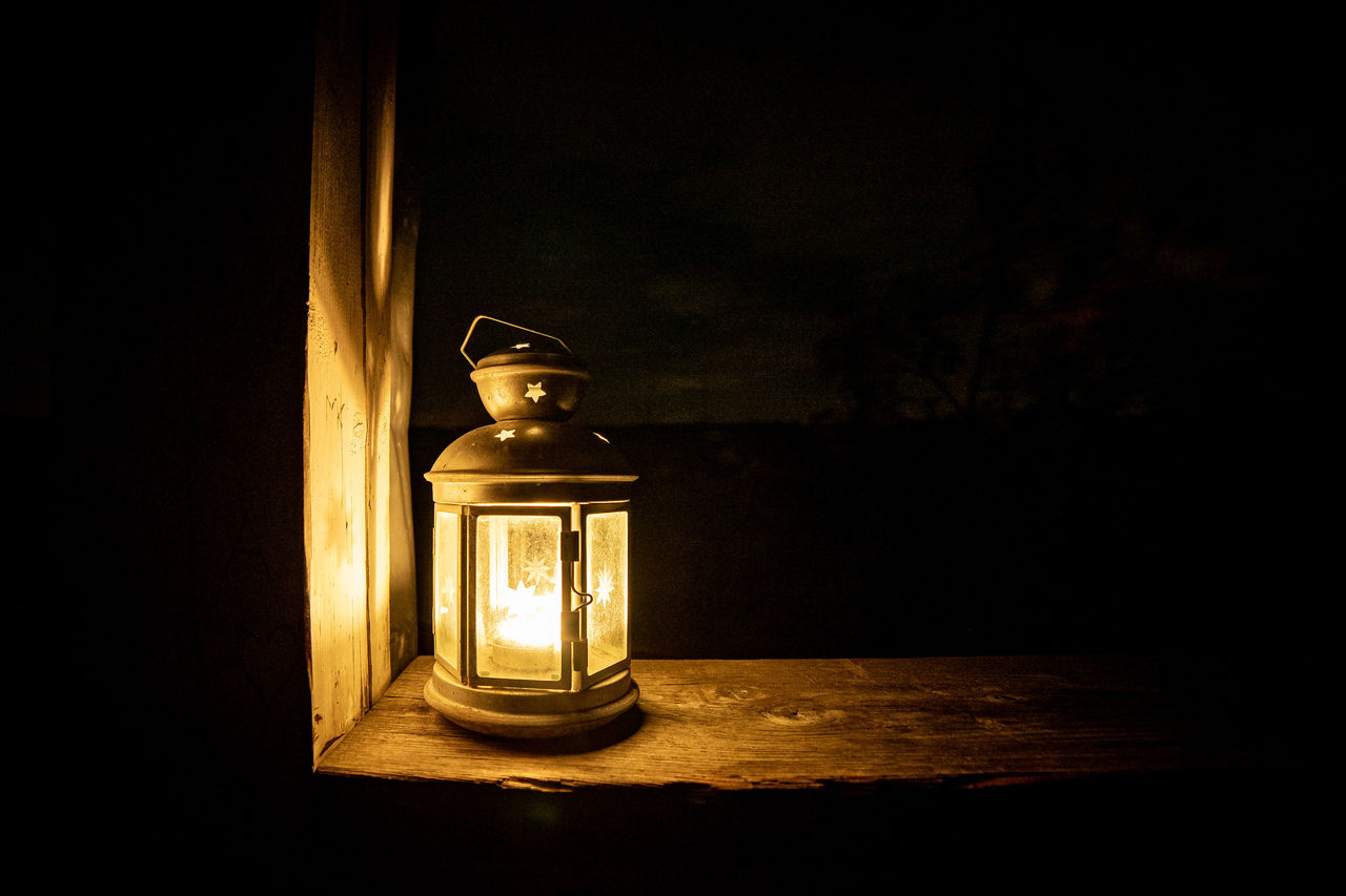 illuminated, table, lighting equipment, indoors, glass - material, dark, container, transparent, still life, no people, close-up, candle, wood - material, night, oil lamp, single object, lantern, glowing, flame, electric lamp, light, black background