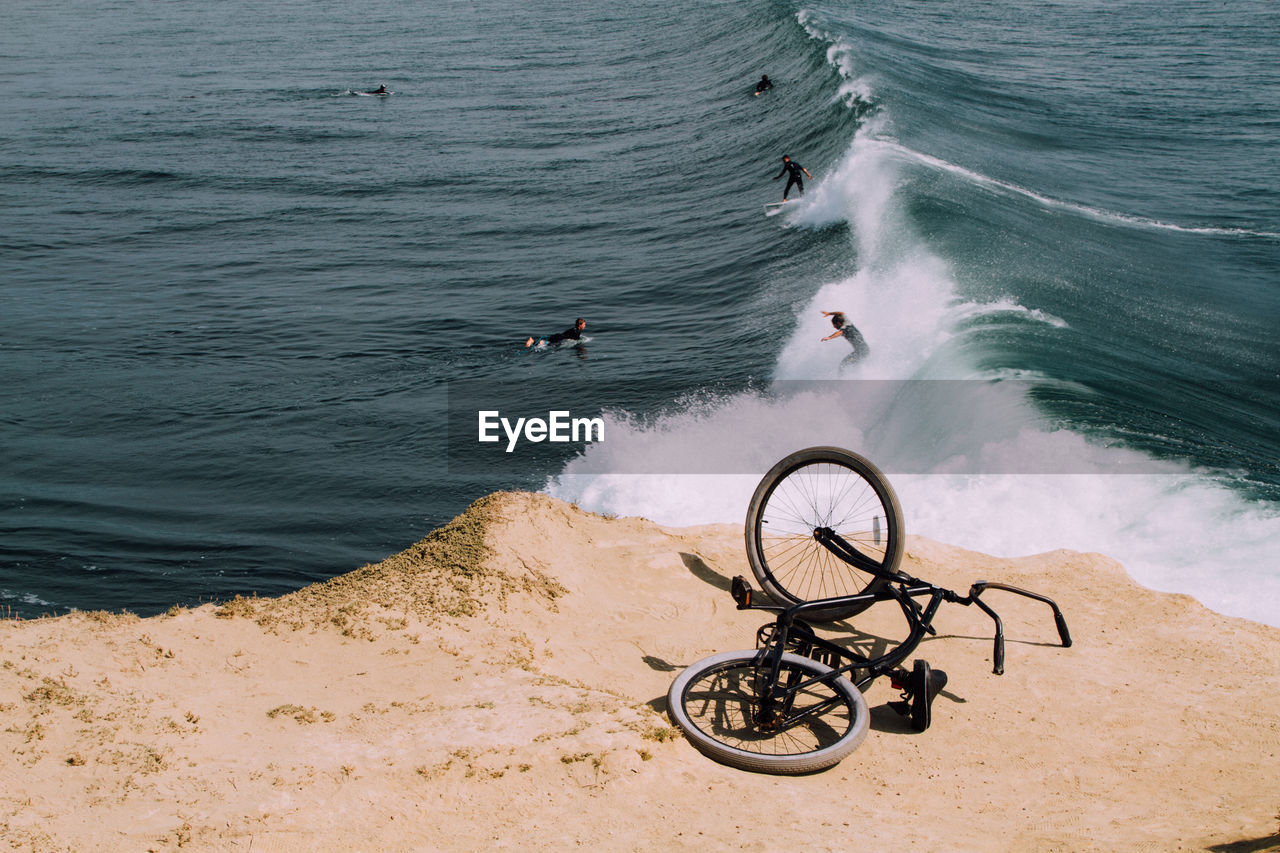 High Angle View Of Bicycle With People Surfing In Sea