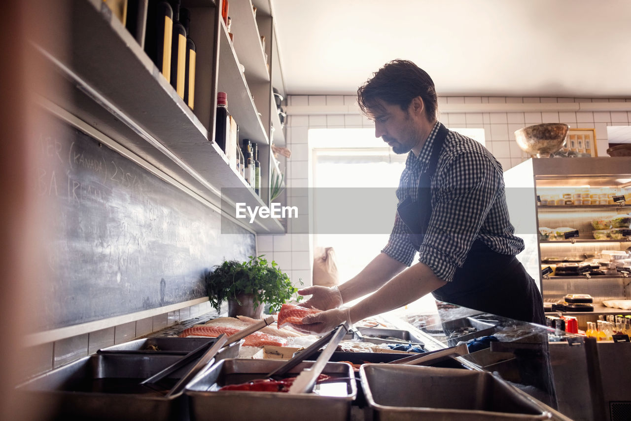 kitchen, one person, domestic room, real people, domestic kitchen, lifestyles, standing, food and drink, casual clothing, home, domestic life, preparation, food, indoors, preparing food, holding, kitchen utensil, appliance, household equipment, housework