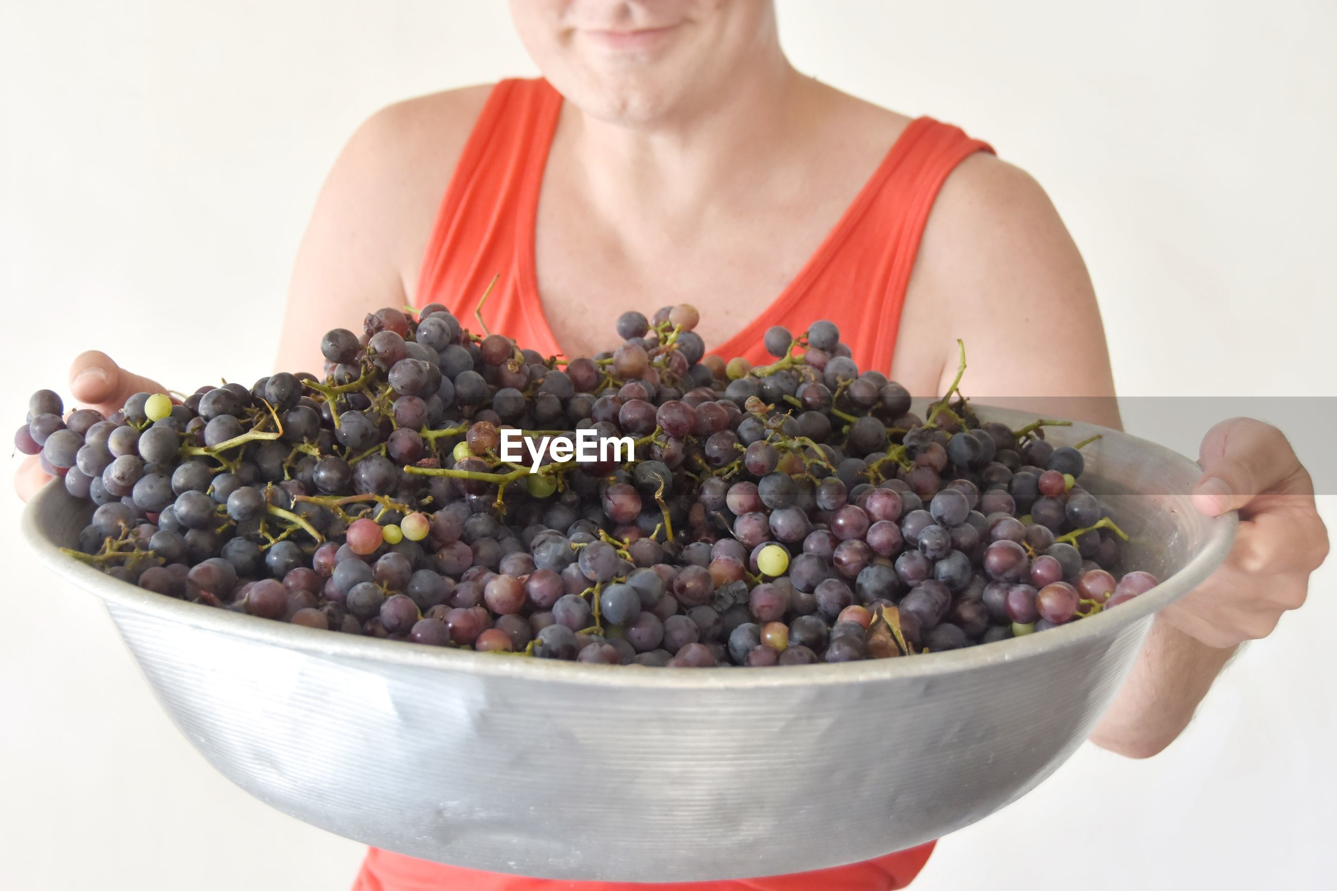 Midsection of woman holding grapes in bowl against white background