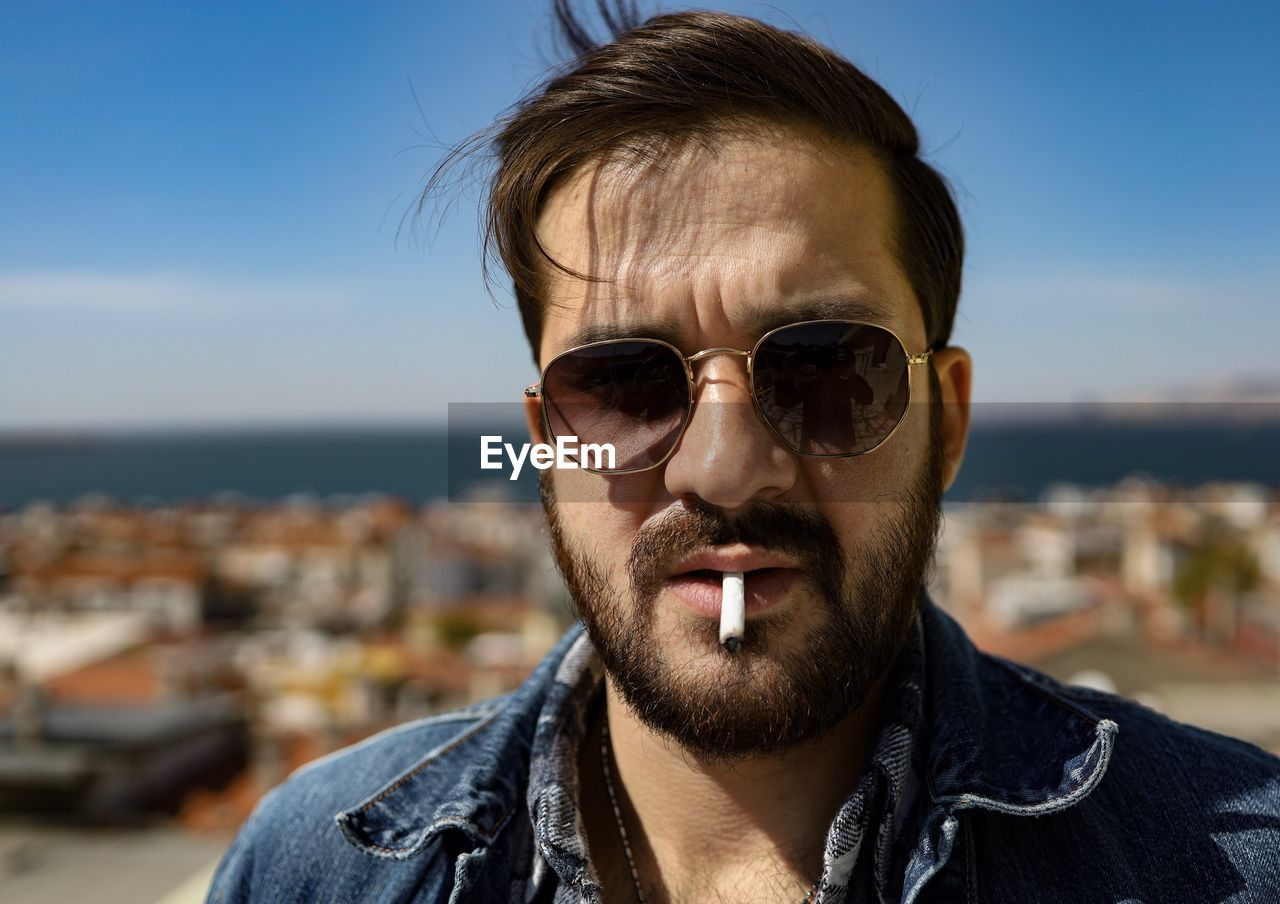 Close-up portrait of man with cigarette in mouth against sky
