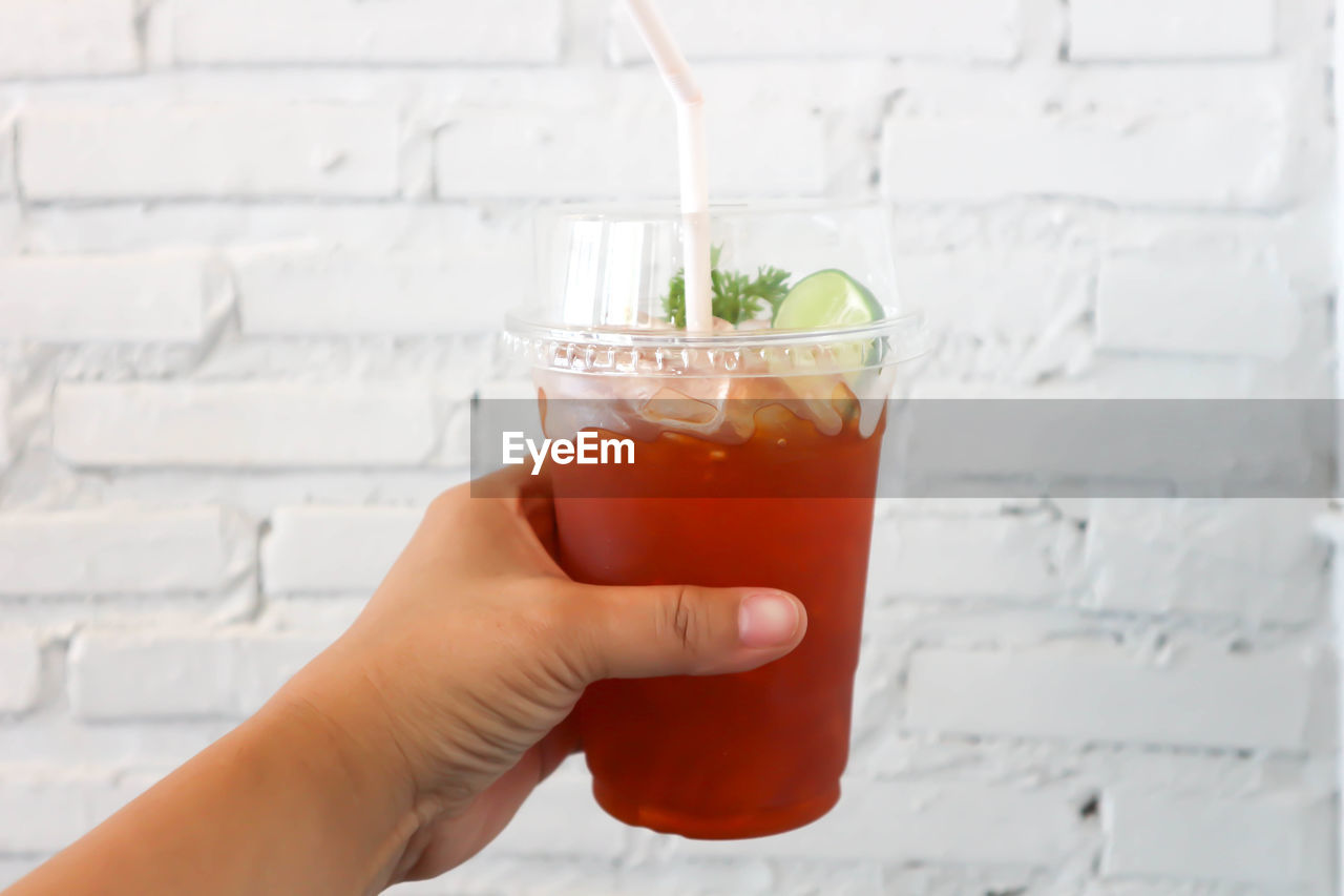human body part, food and drink, human hand, refreshment, holding, hand, glass, real people, drink, straw, drinking glass, drinking straw, freshness, people, household equipment, food, body part, lifestyles, unrecognizable person, cocktail, finger, herb, mint leaf - culinary, human limb