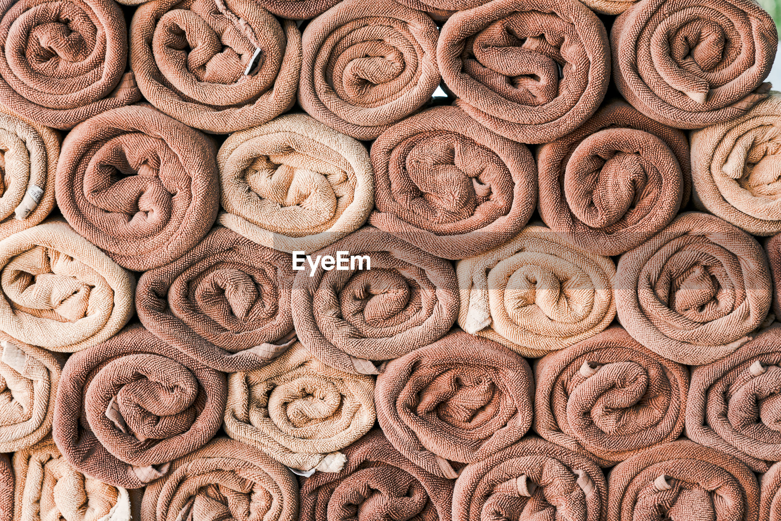 Full frame shot of stacked rolled brown and beige towels