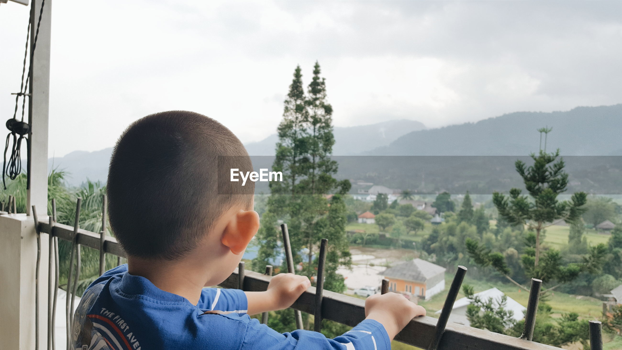 Rear view of boy looking at mountains against cloudy sky through balcony