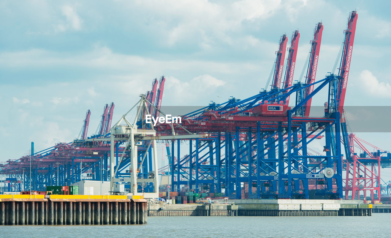 sky, industry, crane - construction machinery, transportation, cloud - sky, built structure, development, architecture, day, shipping, construction site, outdoors, freight transportation, no people, commercial dock, city