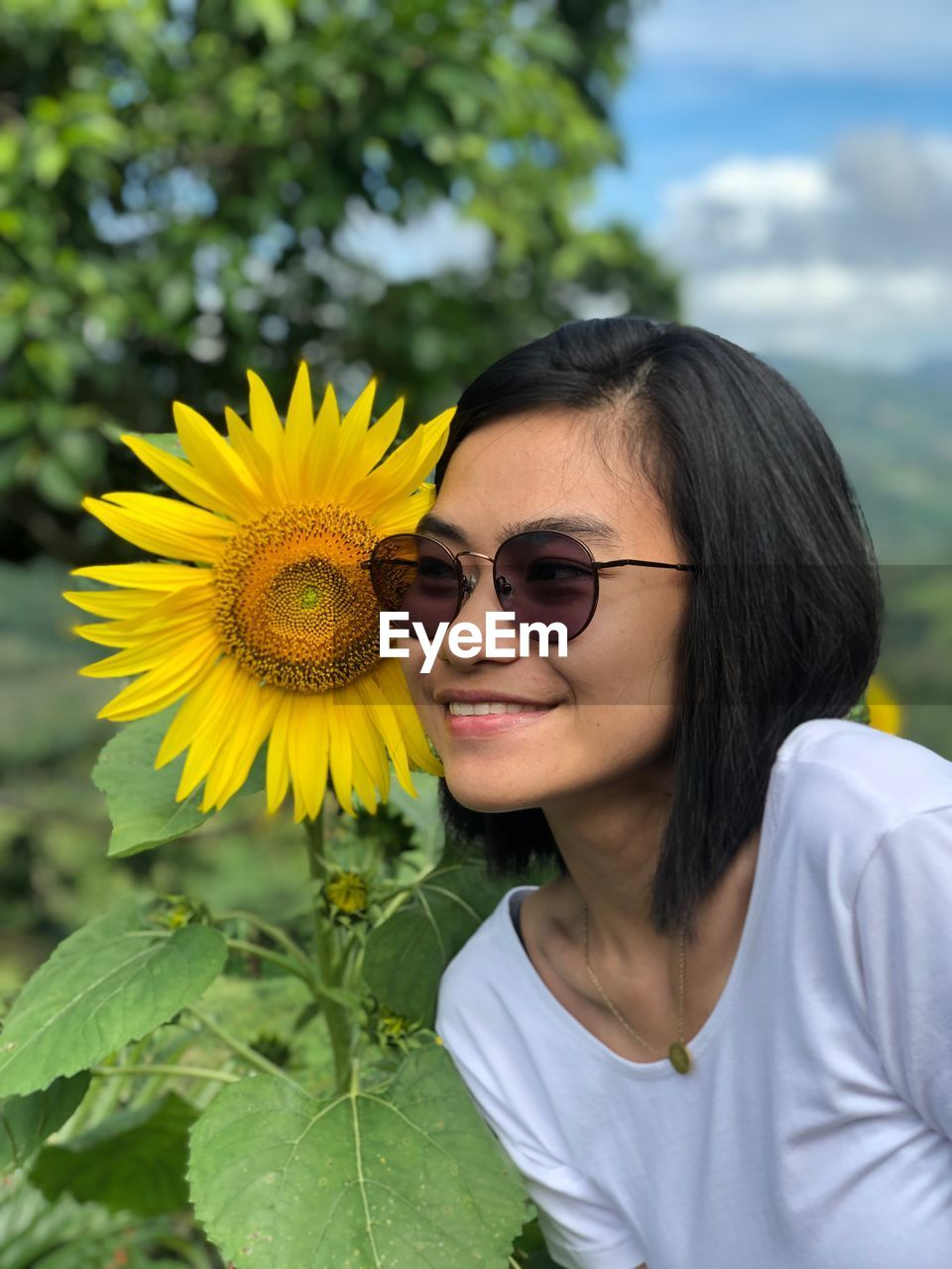 Close-up of smiling young woman wearing sunglasses standing by sunflower
