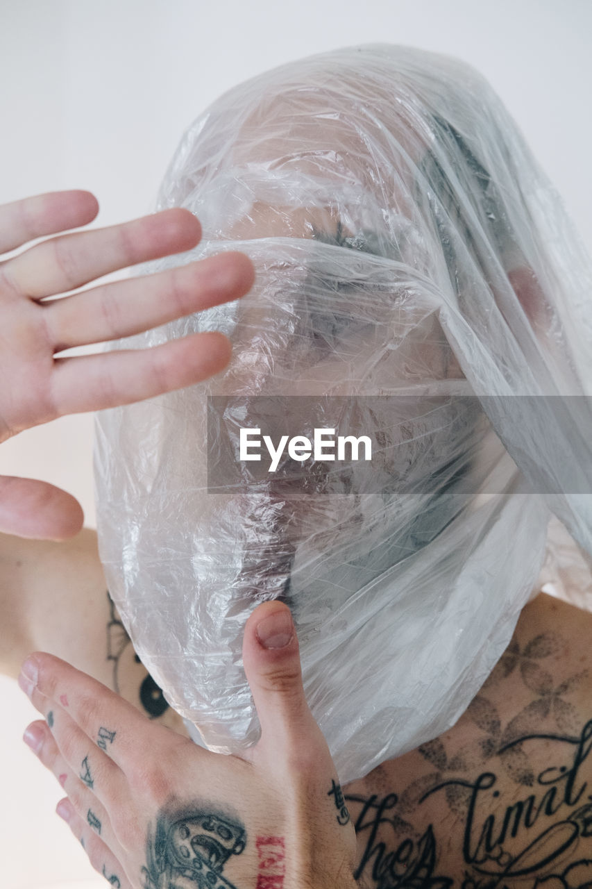 CLOSE-UP PORTRAIT OF WOMAN HAND HOLDING PLASTIC