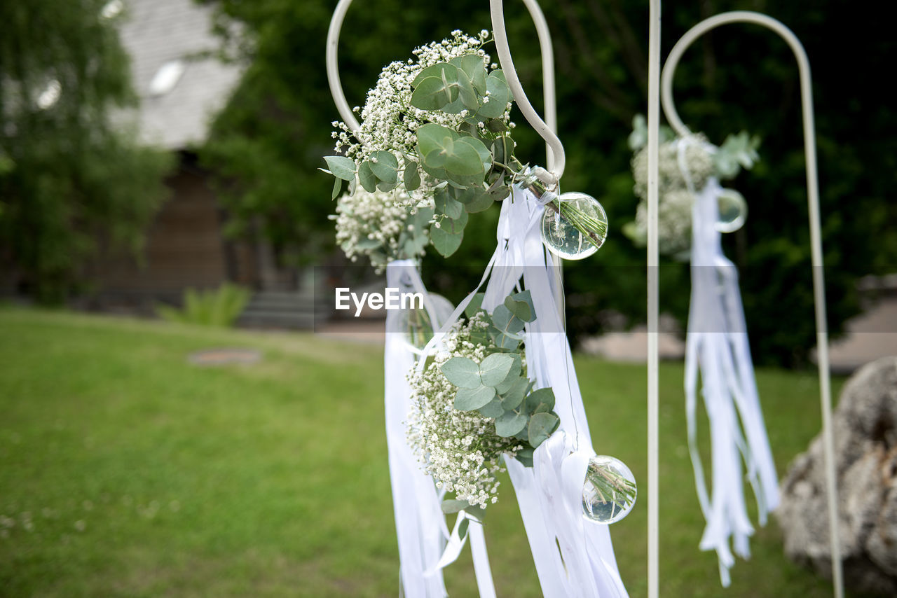 focus on foreground, wedding, plant, white color, celebration, day, nature, event, grass, life events, flower, outdoors, flowering plant, ceremony, wedding dress, close-up, newlywed, wedding ceremony, celebration event