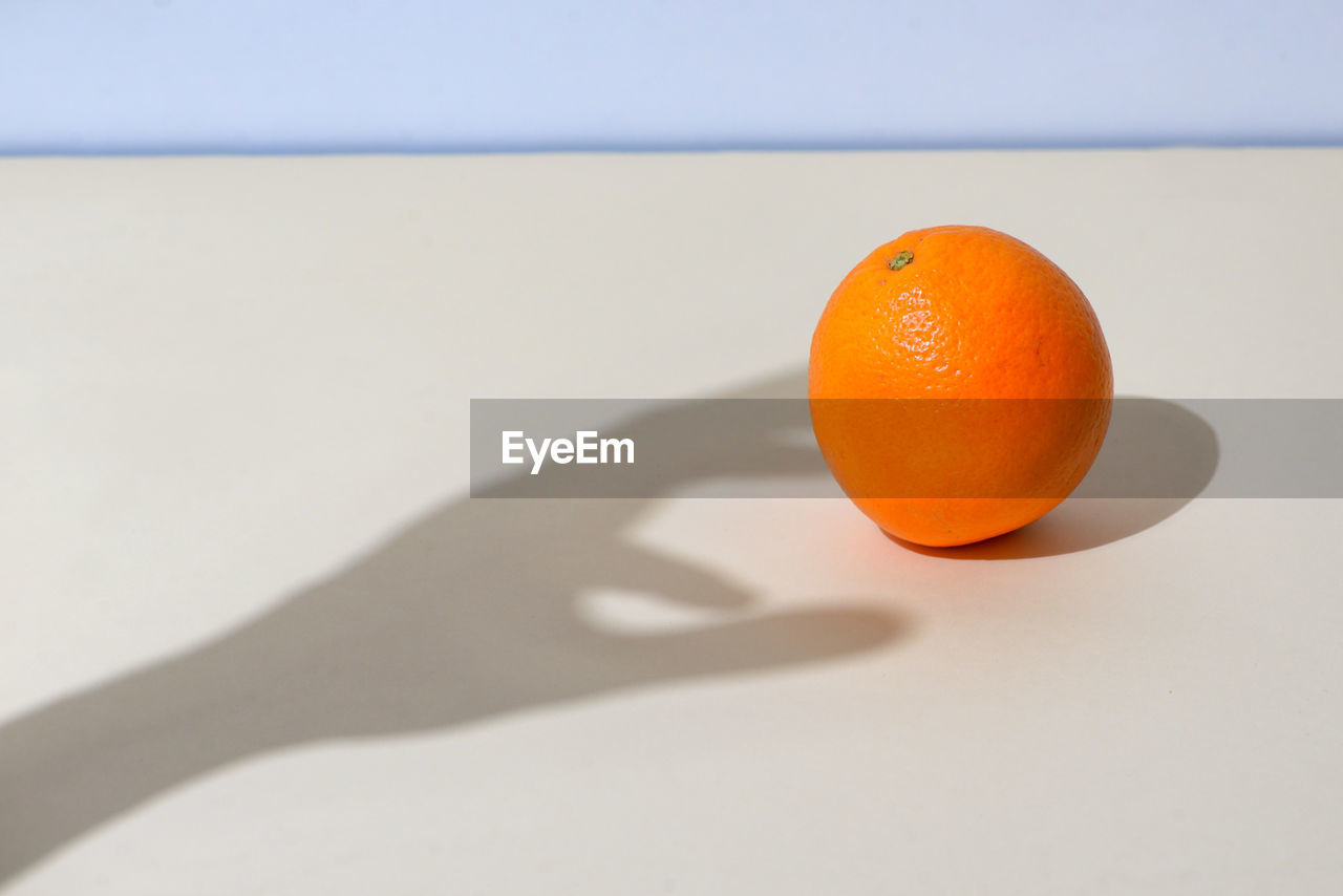 orange color, fruit, citrus fruit, orange, shadow, healthy eating, orange - fruit, wellbeing, food and drink, food, close-up, freshness, no people, still life, sunlight, indoors, nature, table, high angle view, white color