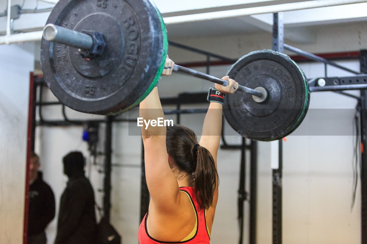Rear View Of A Woman Exercising With Barbell