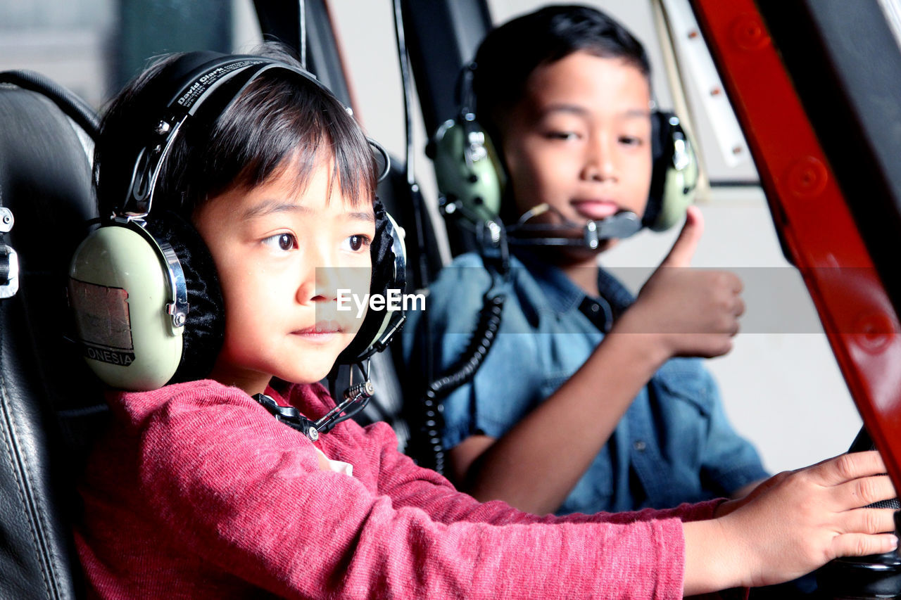 Siblings Sitting In Helicopter