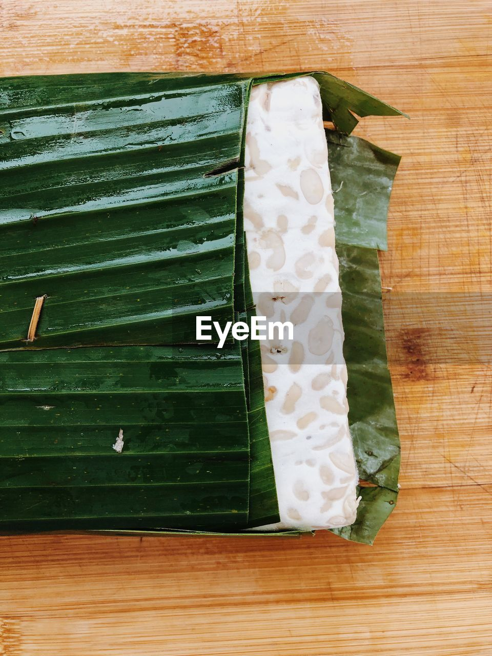 leaf, green color, no people, plant part, food, wood - material, food and drink, directly above, freshness, still life, indoors, close-up, high angle view, white color, banana leaf, table, nature, plant, leaves, flooring