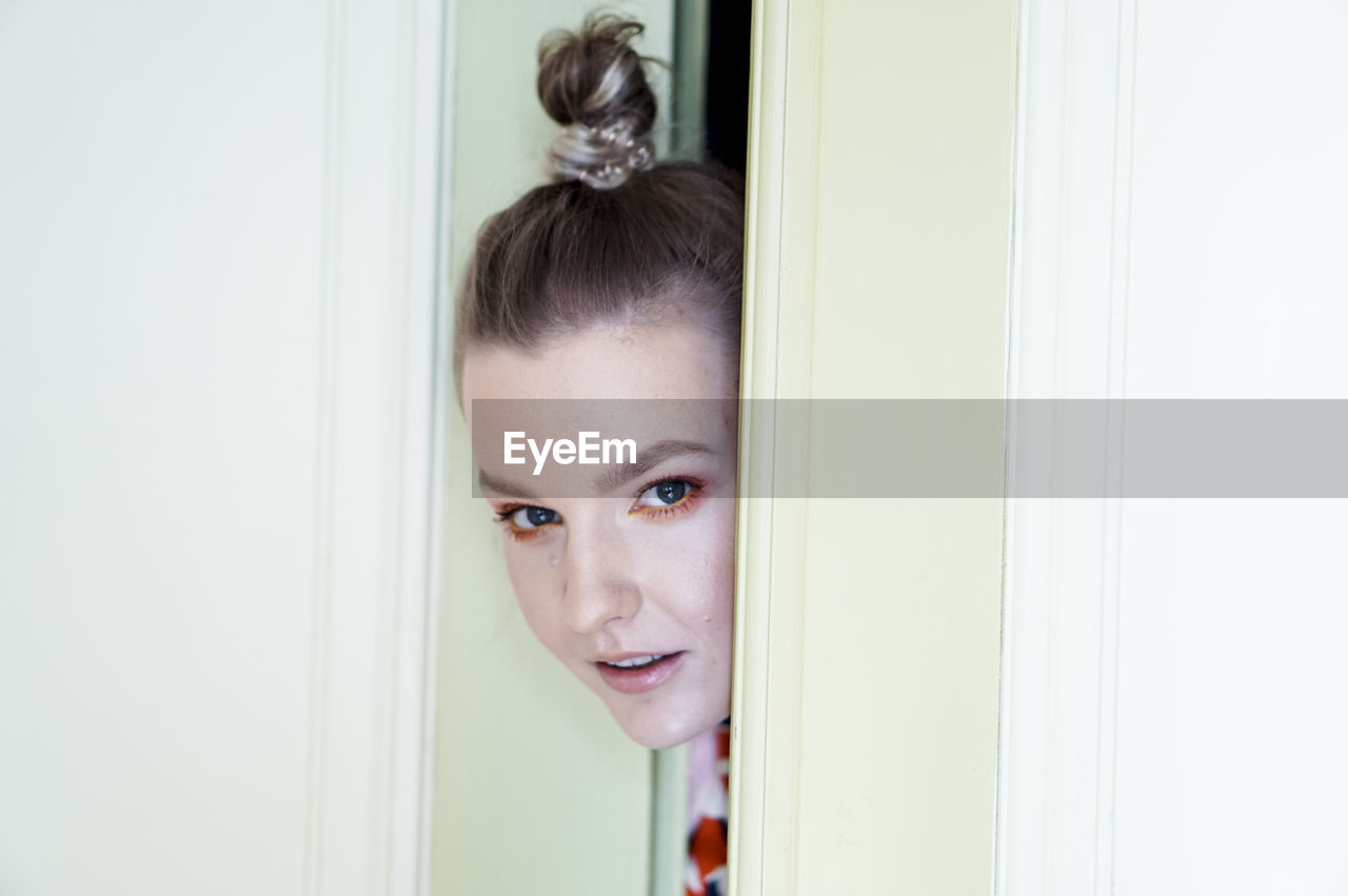 Close-up portrait of woman with make-up looking through door