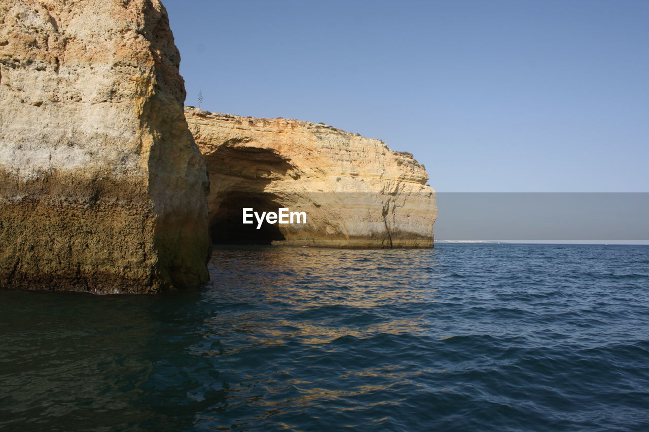 sea, rock formation, nature, waterfront, rock - object, water, beauty in nature, tranquility, scenics, tranquil scene, no people, natural arch, day, outdoors, clear sky, sky