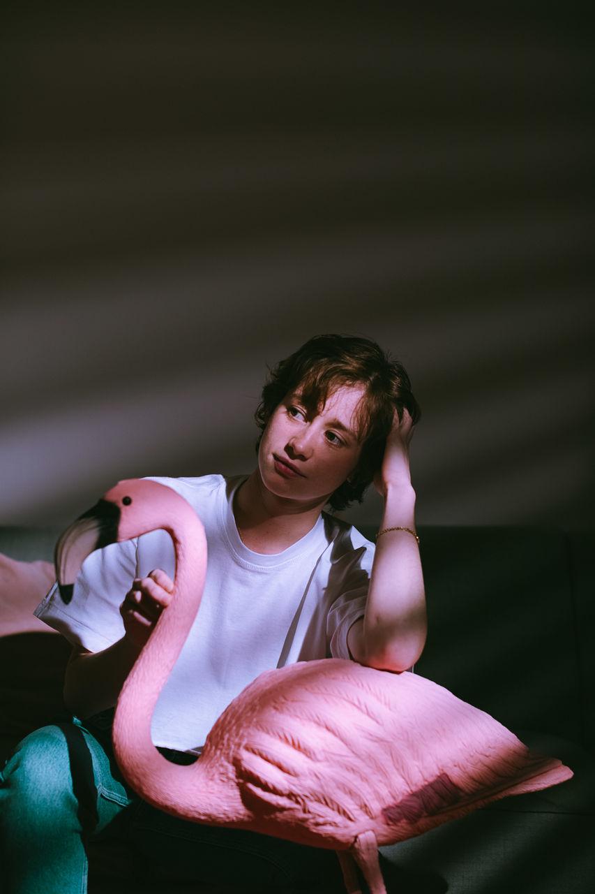 Thoughtful woman holding flamingo sculpture in darkroom