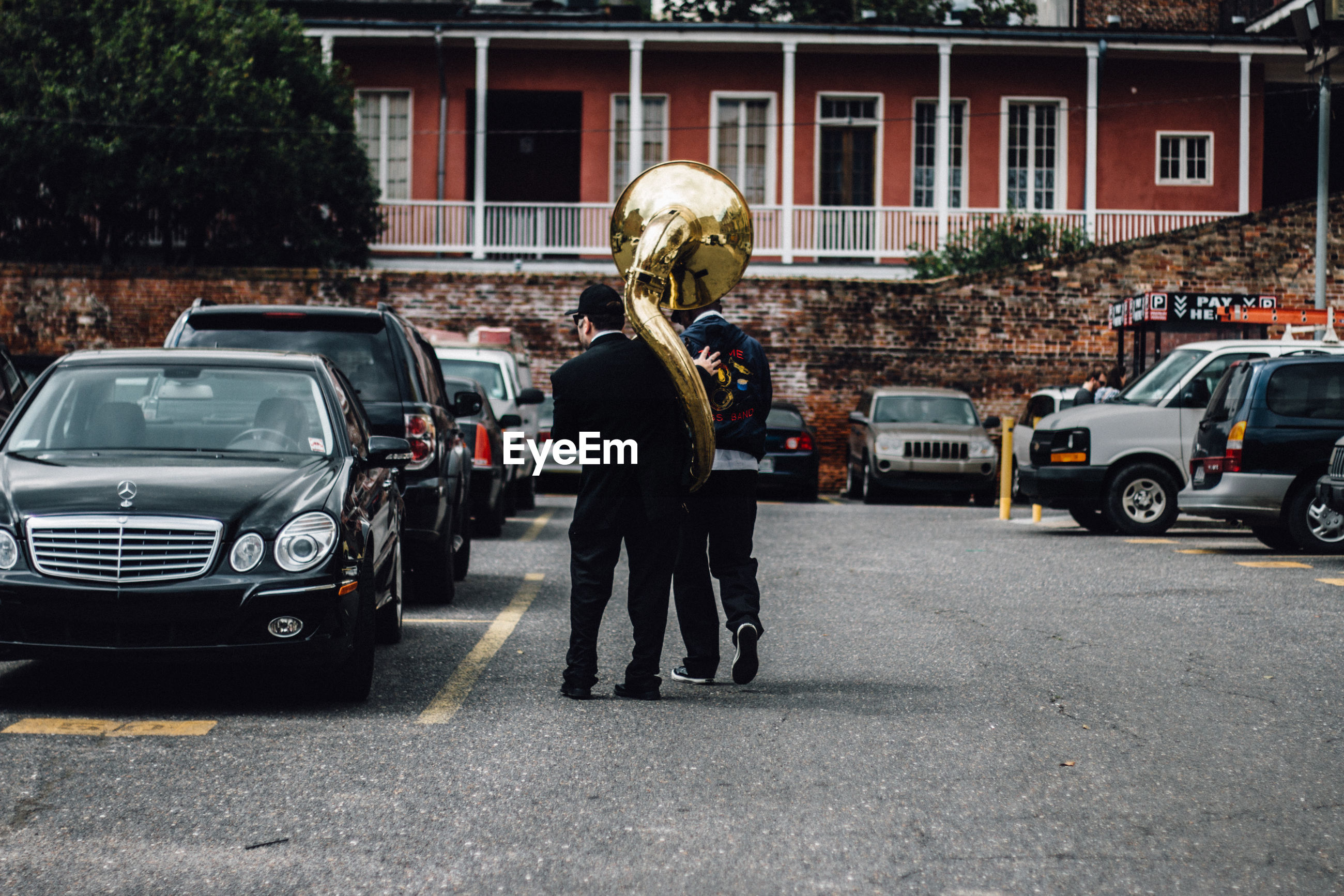 Rear view of man with friend carrying brass instrument in parking lot