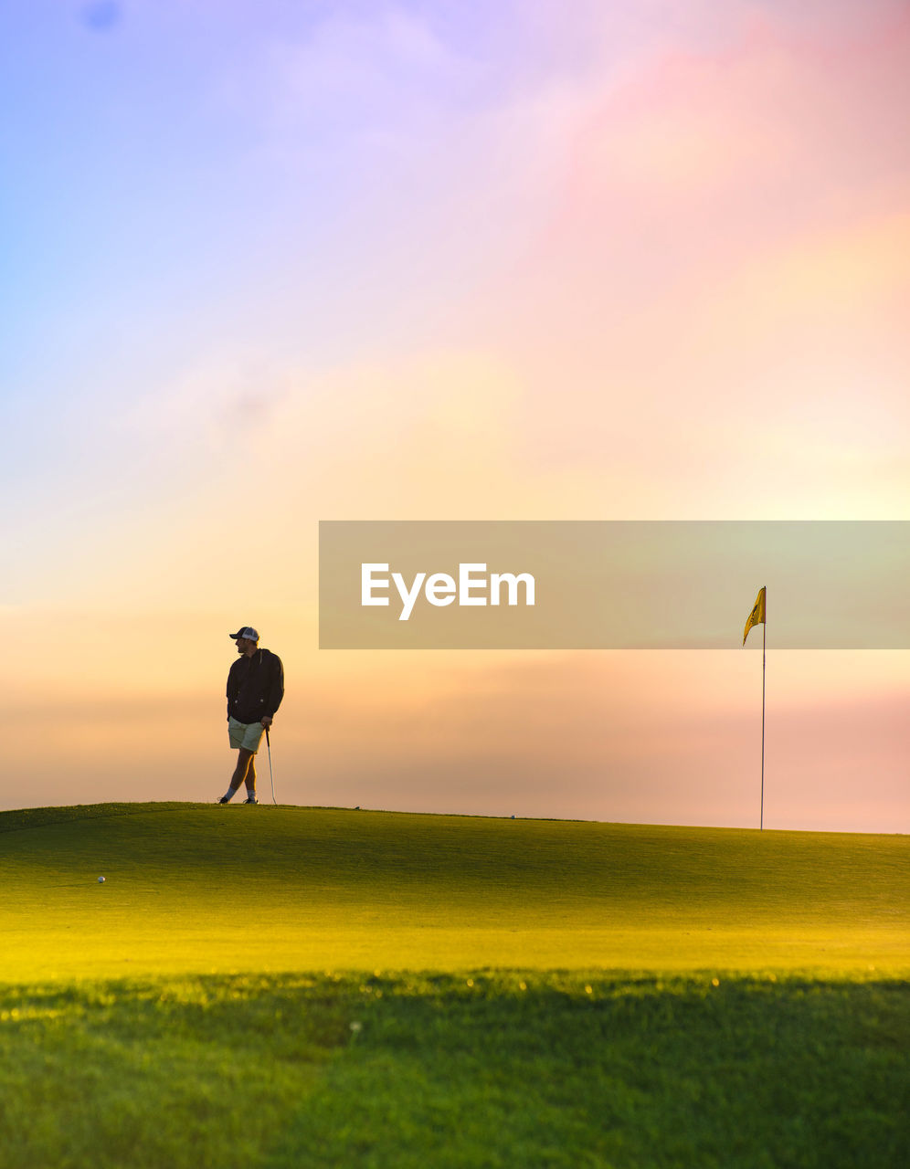 Man Standing On Golf Field Against Sky During Sunset