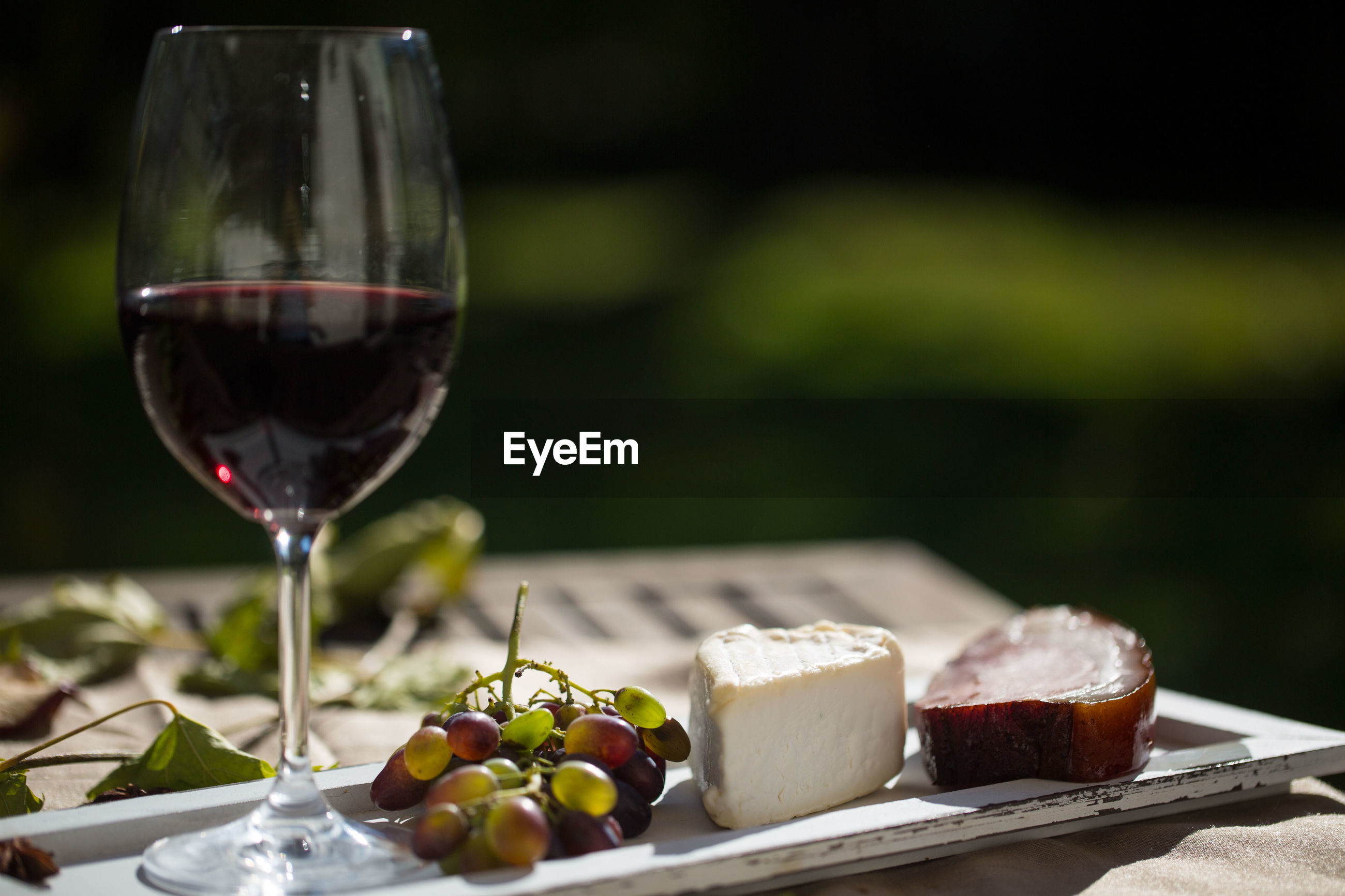 Close-up of red wine and cheese on wooden table