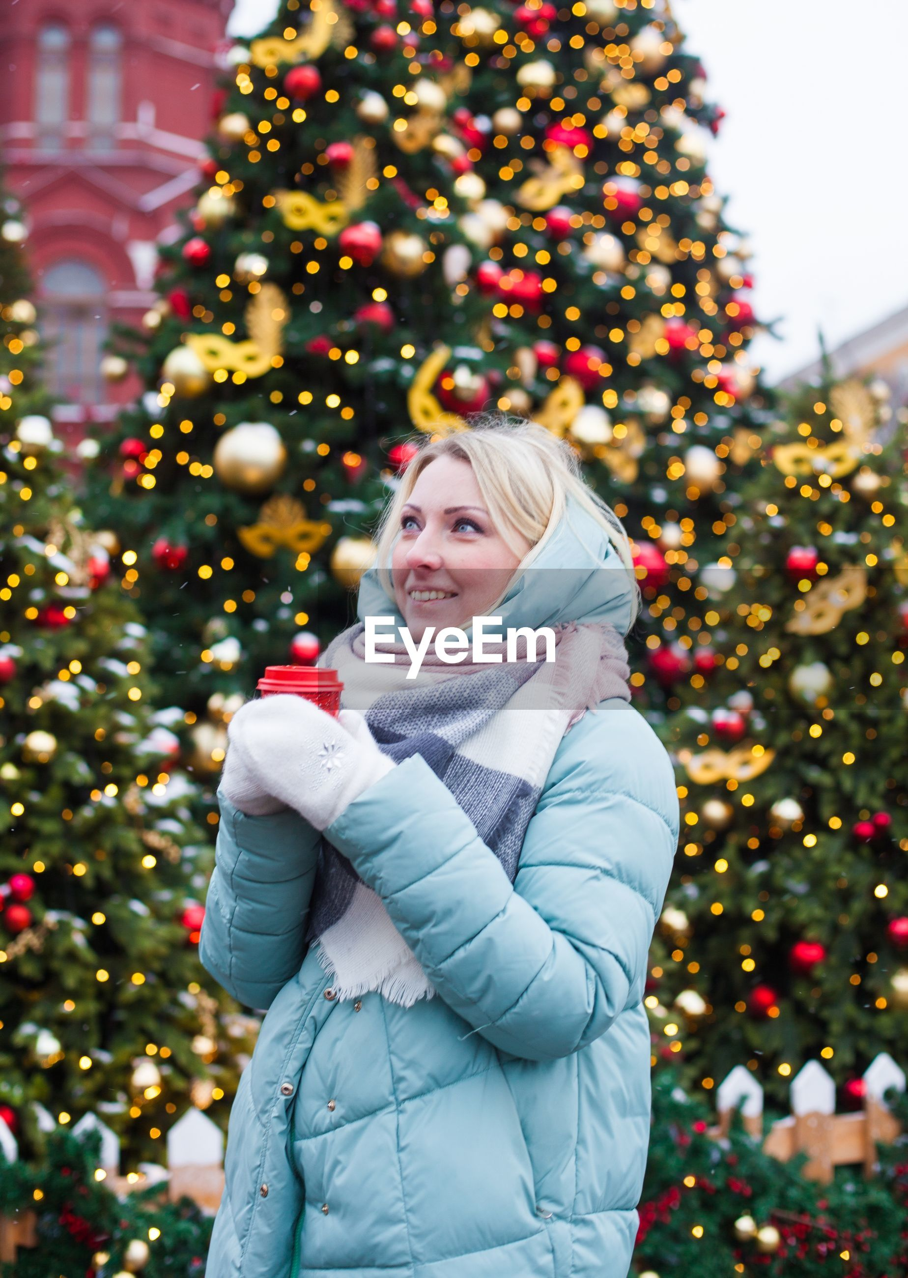 Woman looking away while standing against christmas tree during winter