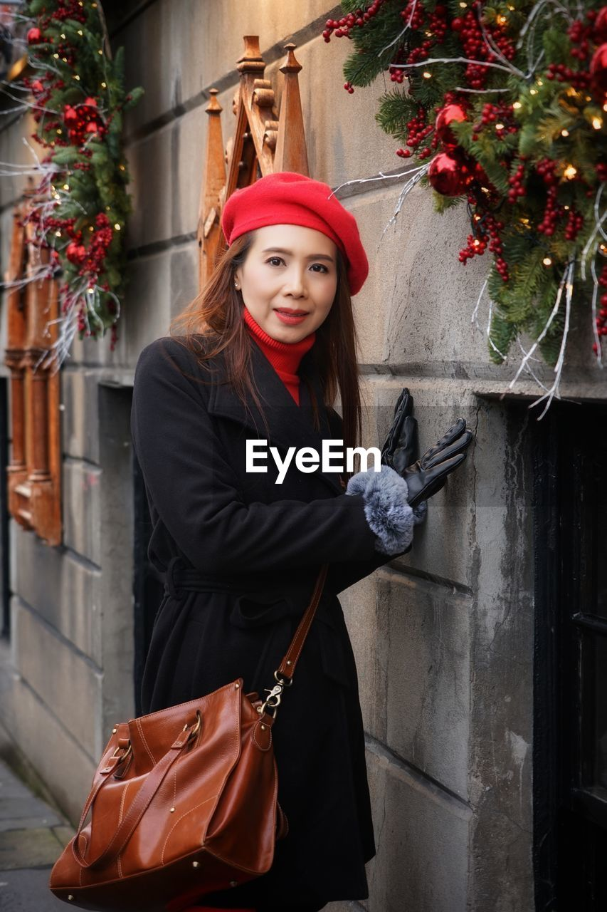 Portrait of woman standing by wall during christmas