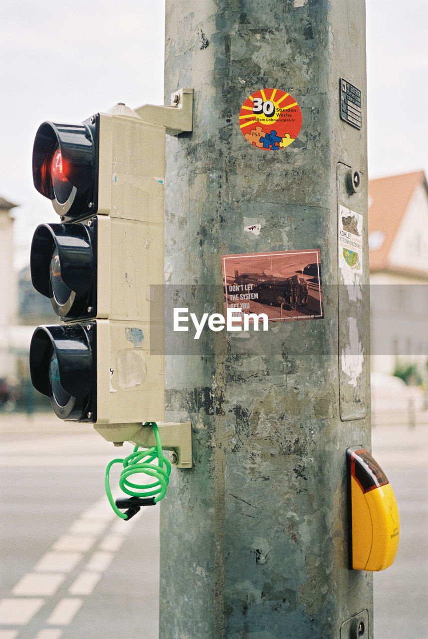 focus on foreground, safety, security, close-up, day, no people, protection, technology, control, outdoors, road signal, metal, architecture, built structure, building exterior, guidance, lighting equipment, green color, sign, push button
