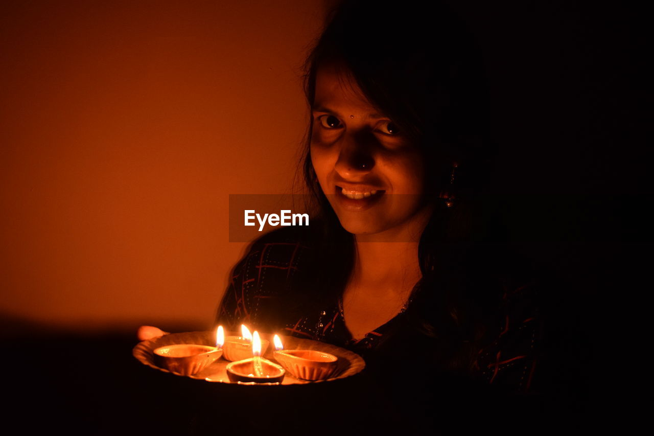flame, burning, candle, fire, one person, illuminated, glowing, front view, headshot, indoors, lifestyles, smiling, real people, celebration, portrait, leisure activity, orange color, fire - natural phenomenon, heat - temperature, happiness, dark, birthday candles