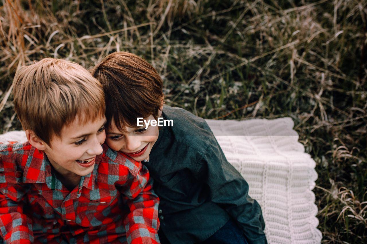 Cheerful siblings sitting in park