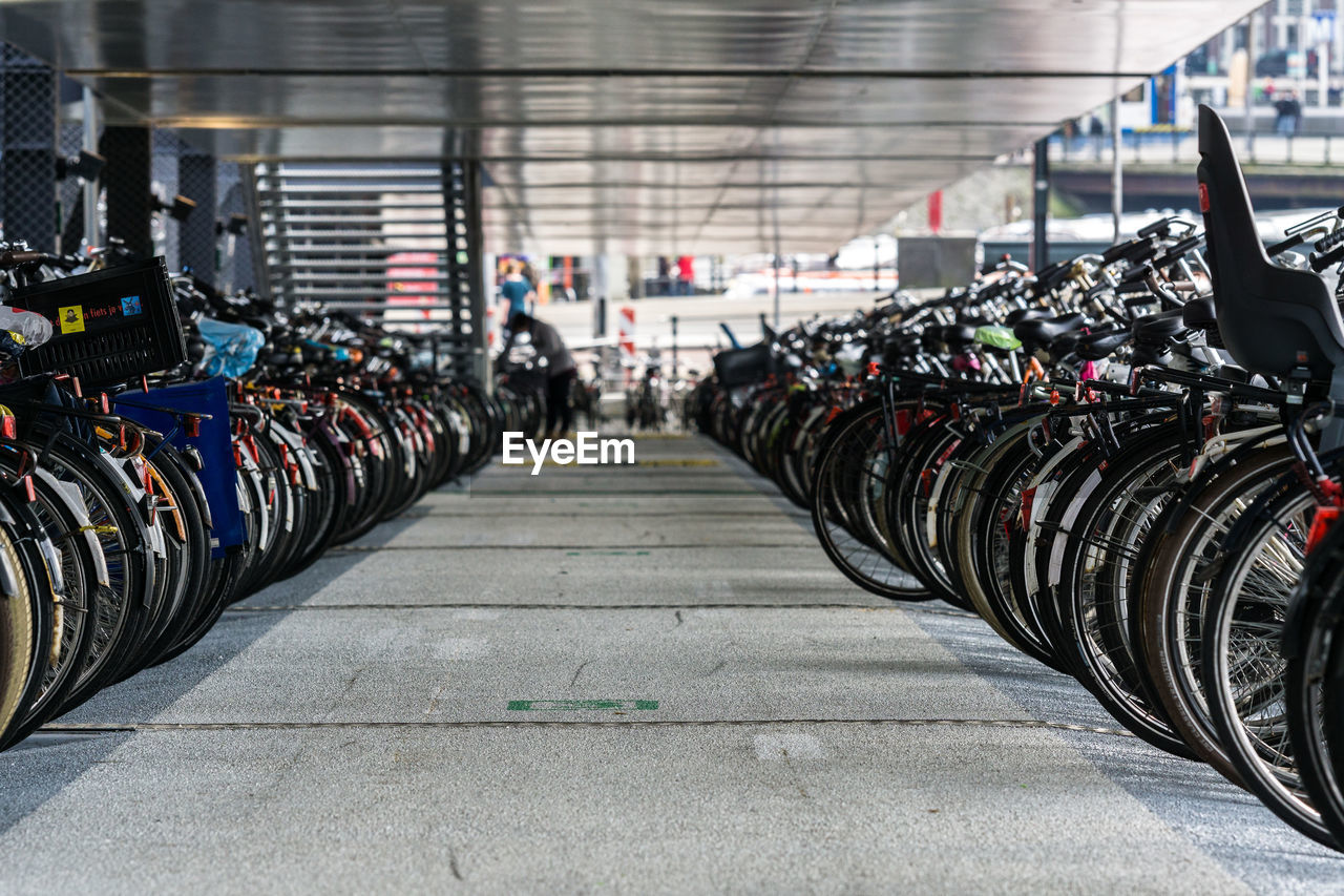 in a row, transportation, mode of transportation, large group of objects, land vehicle, stationary, focus on foreground, parking lot, abundance, parking, incidental people, day, bicycle, wheel, side by side, bicycle rack, architecture, outdoors, order, arrangement, tire