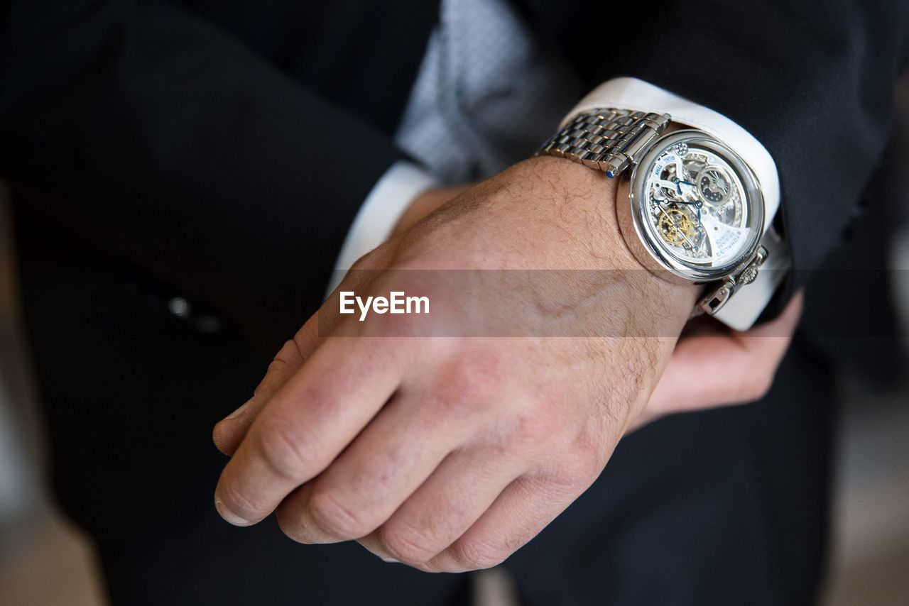 hand, human hand, watch, time, wristwatch, men, real people, midsection, human body part, one person, focus on foreground, well-dressed, close-up, lifestyles, business, suit, indoors, males, adult, personal accessory, finger