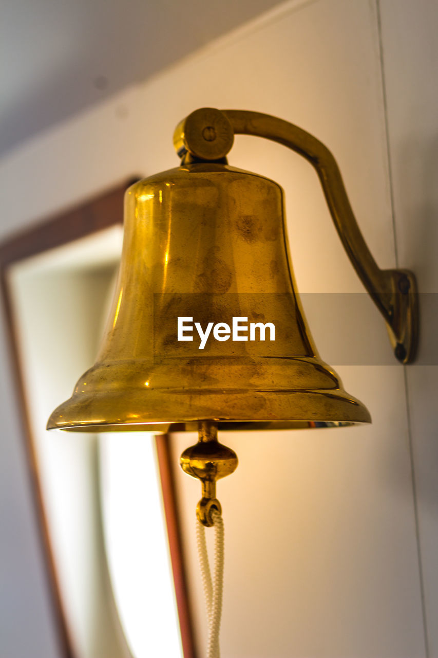 bell, indoors, metal, no people, lighting equipment, hanging, gold colored, wall - building feature, close-up, electric lamp, still life, focus on foreground, lamp shade, decoration, low angle view, antique, single object, table, glass - material, ceiling