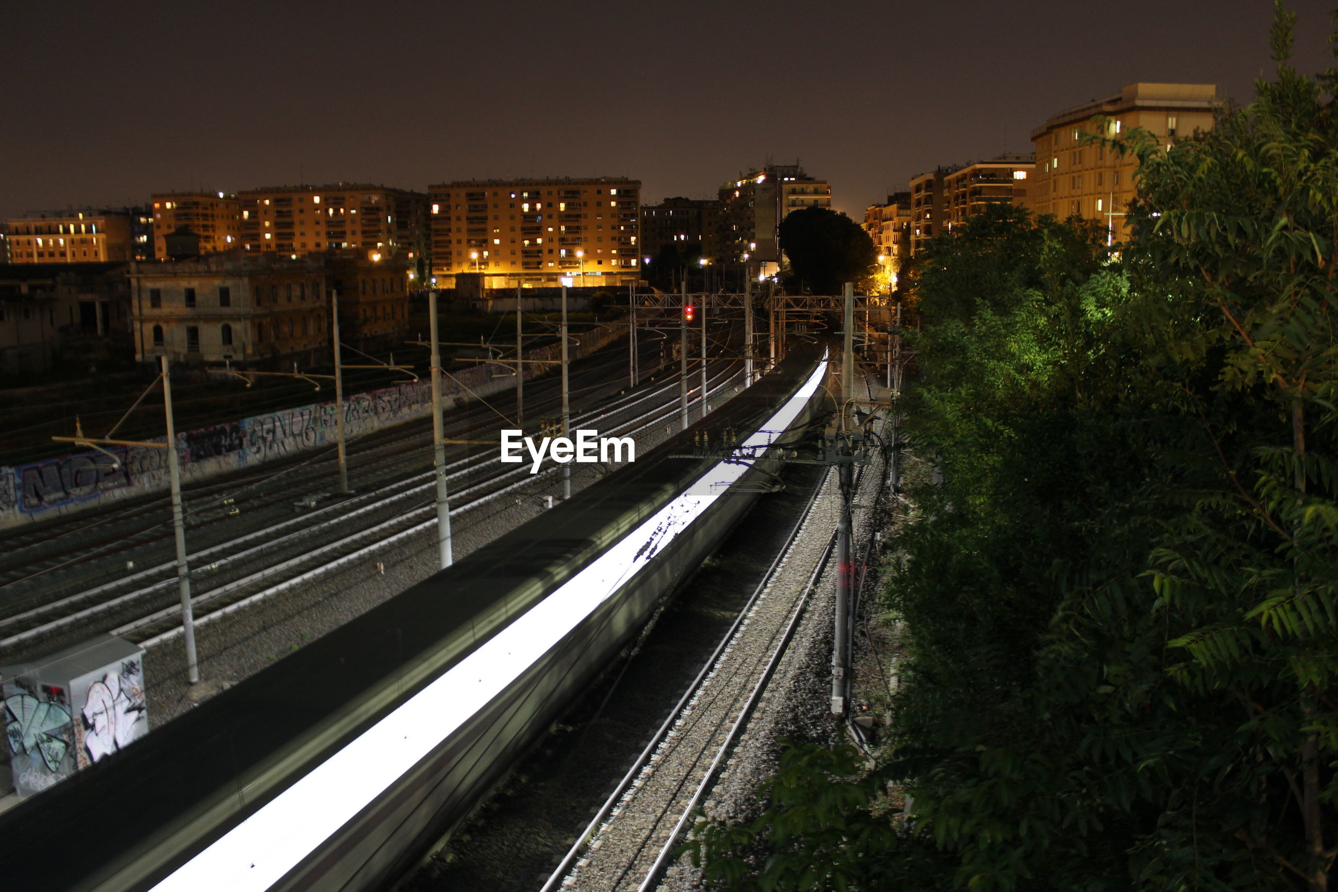 High angle view of train moving on railroad tracks in illuminated city at night