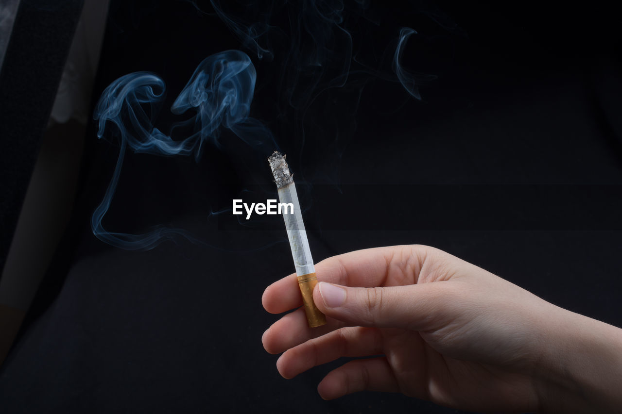 Cropped hand of person holding cigarette against black background