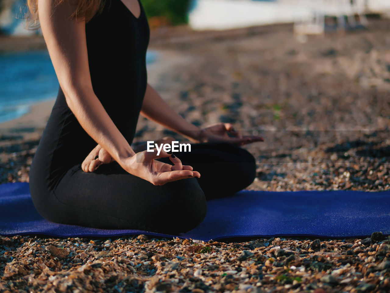 Low section of woman doing yoga at beach