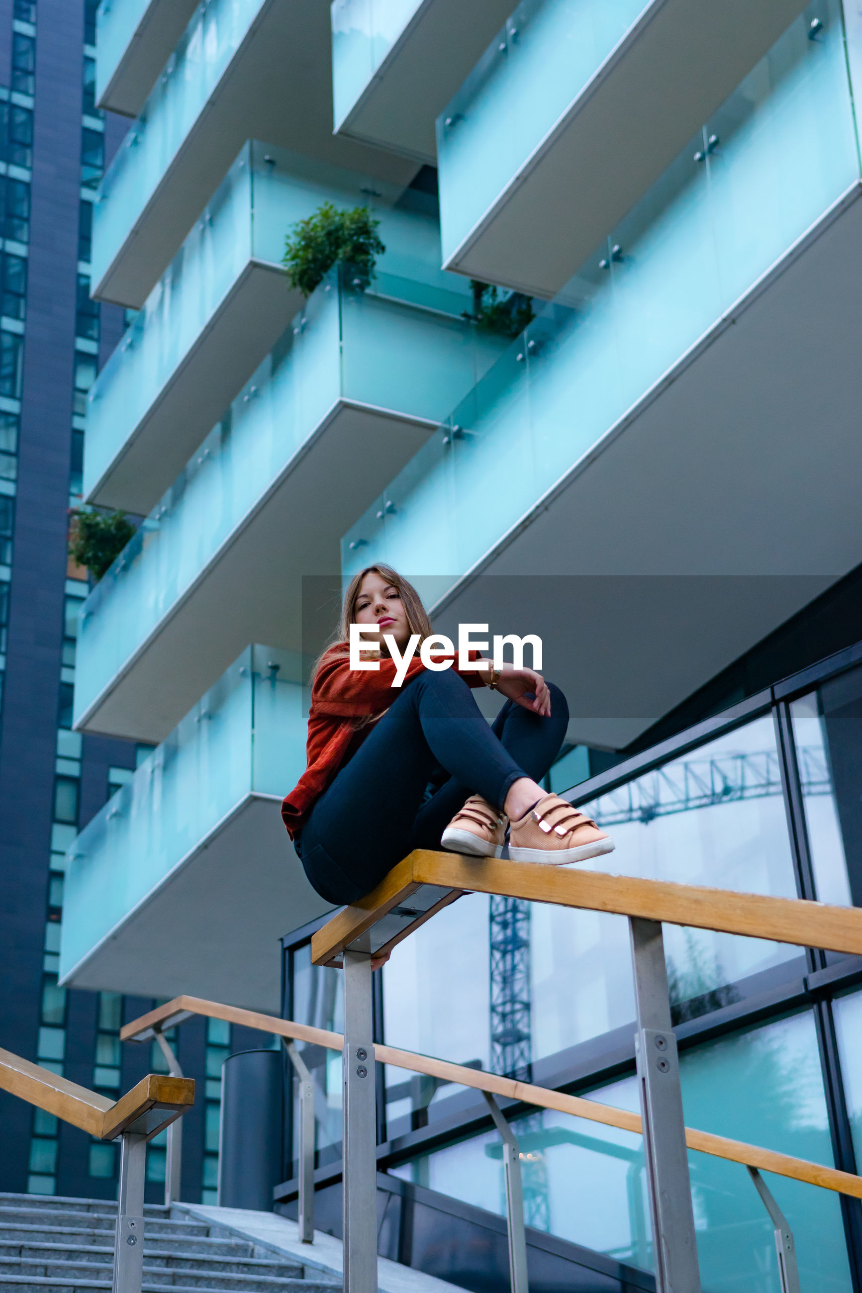 Low angle view of woman sitting on railing against building in city