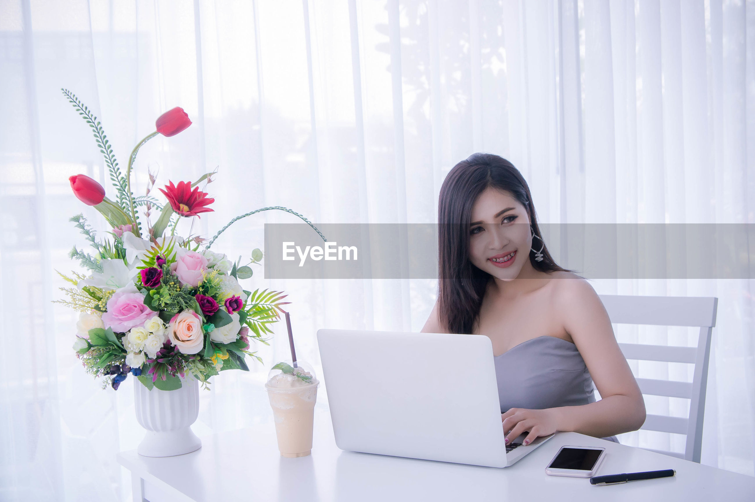 Smiling young woman using laptop on table at home